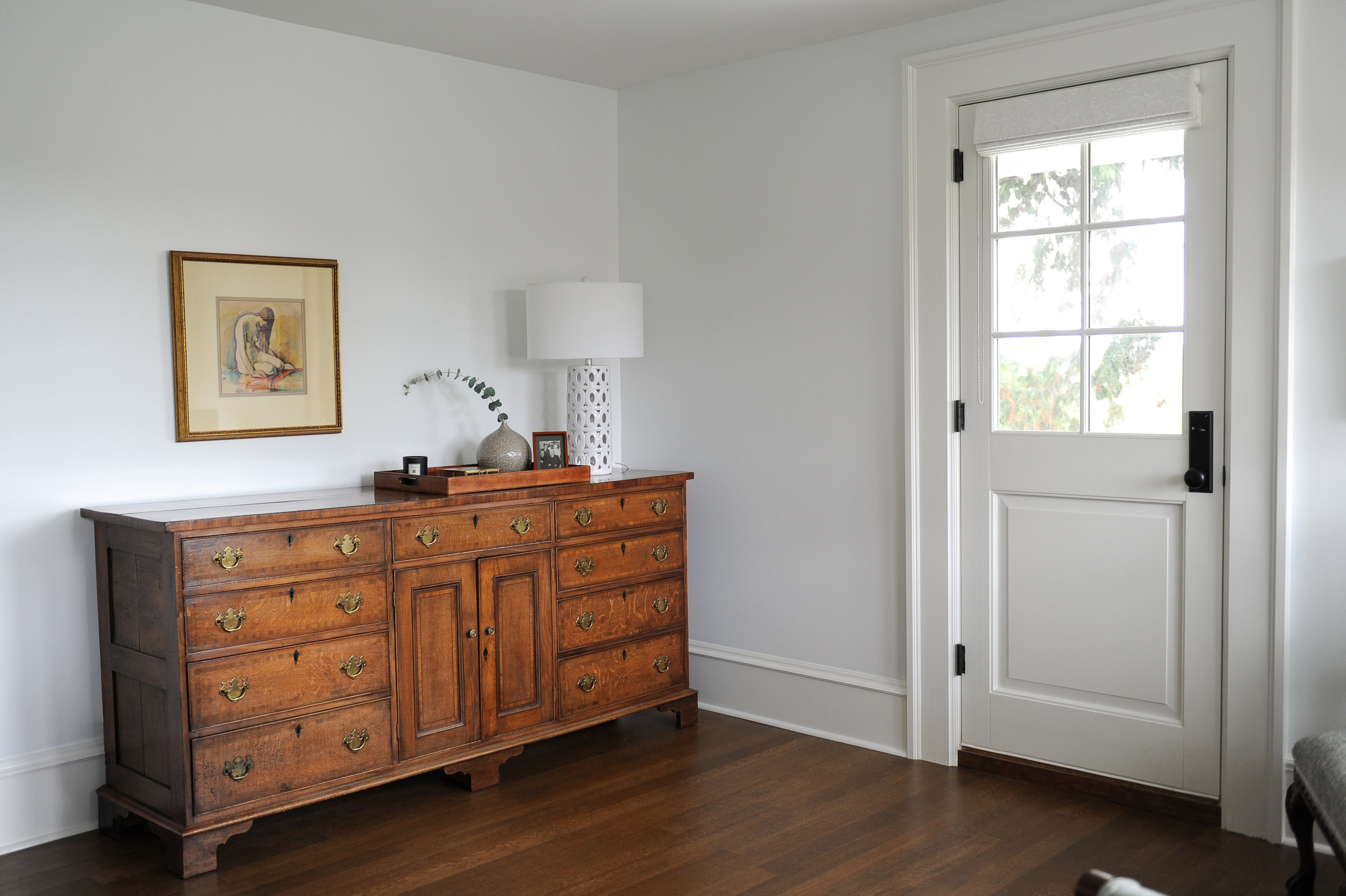 An antique wooden dresser sits in the corner of a bedroom. A white lamp and a wooden tray with various decor sit on top of it. A framed painting hangs above it. Near it, there is a white door that leads to the outside.