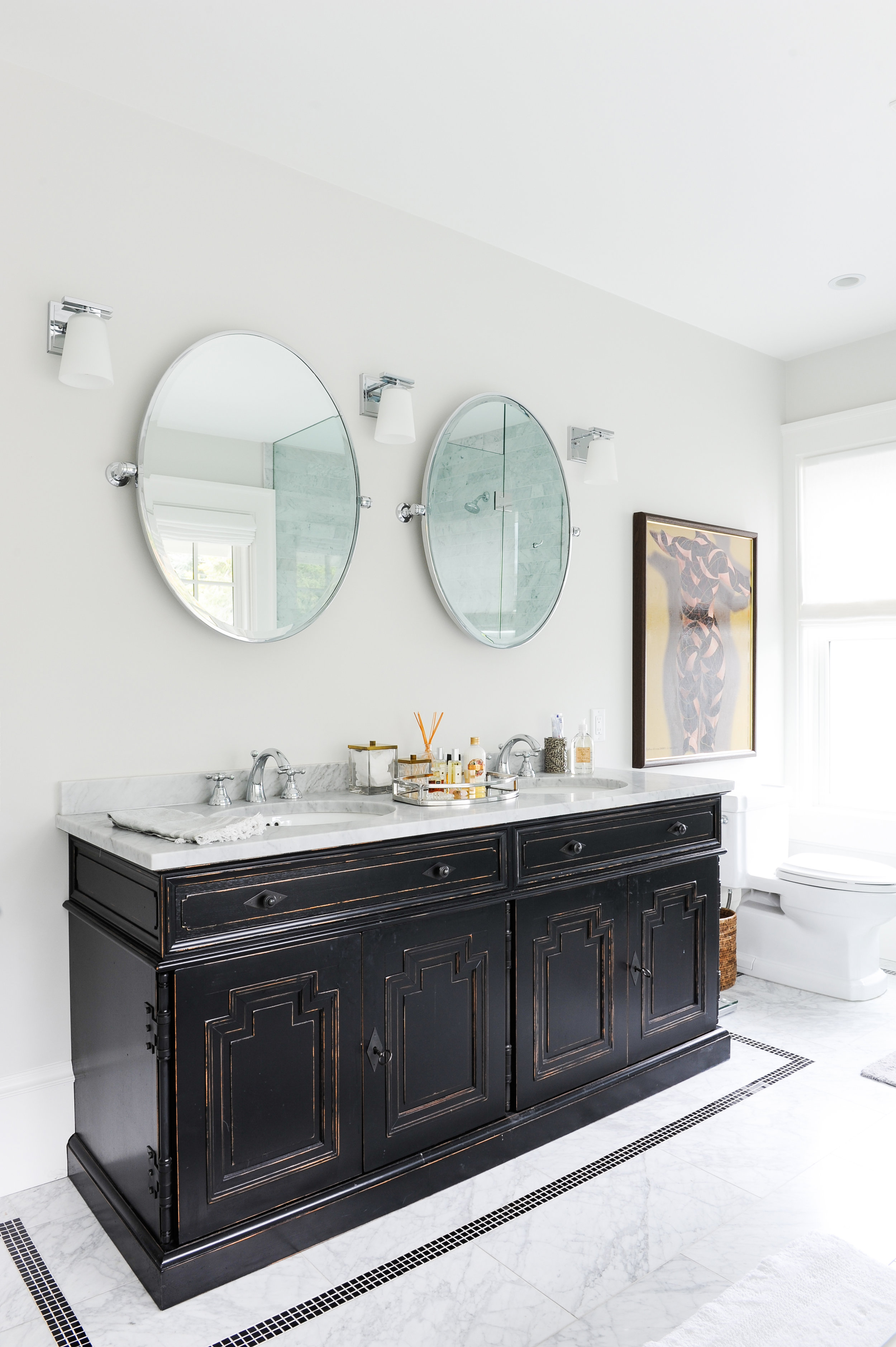 His and hers sinks fitted into a dark wood antique cabinet fill this bathroom. Above the sinks hang two large round vanity mirrors. A brown and yellow painting hangs to the right of the vanity above the toilet.