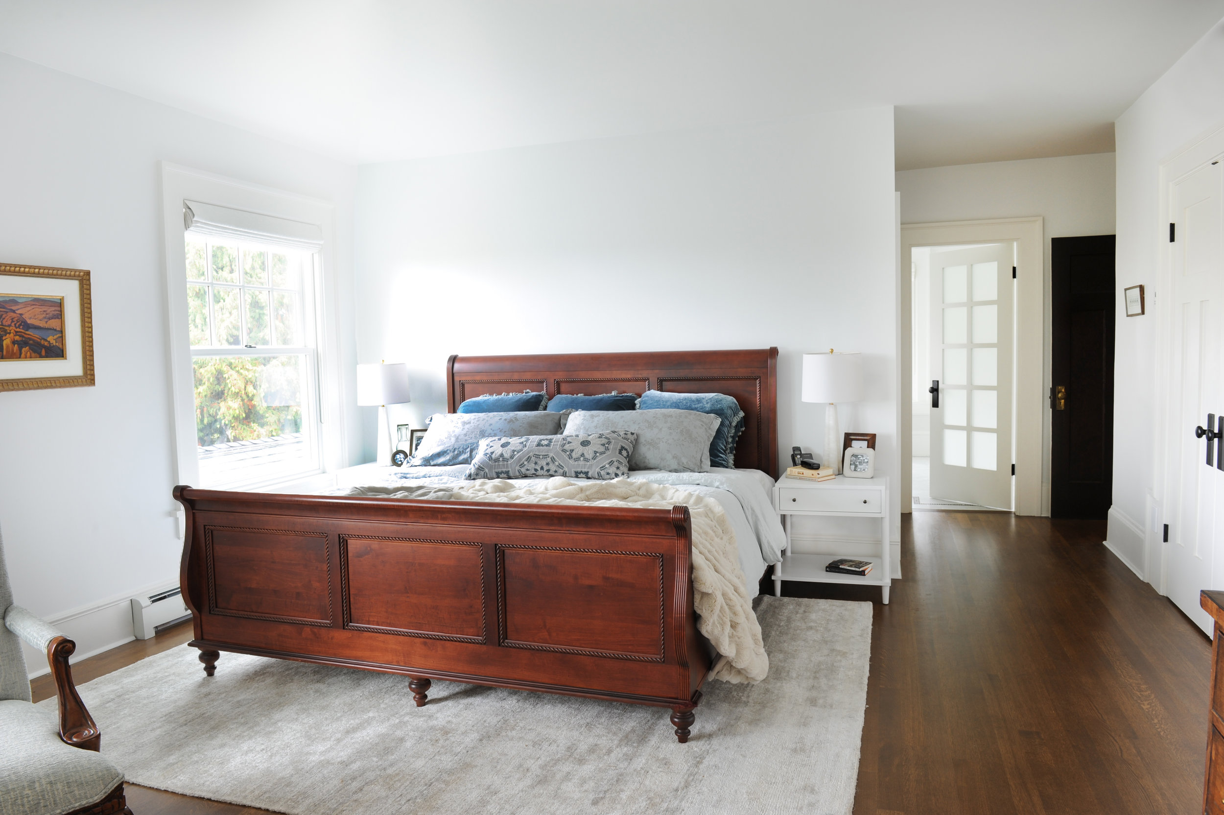 A rich dark wood sleigh bed sits in a bedroom on top of a large area rug. There is a large window to the right of the bed. Beside the window hangs a landscape painting in a wooden frame.