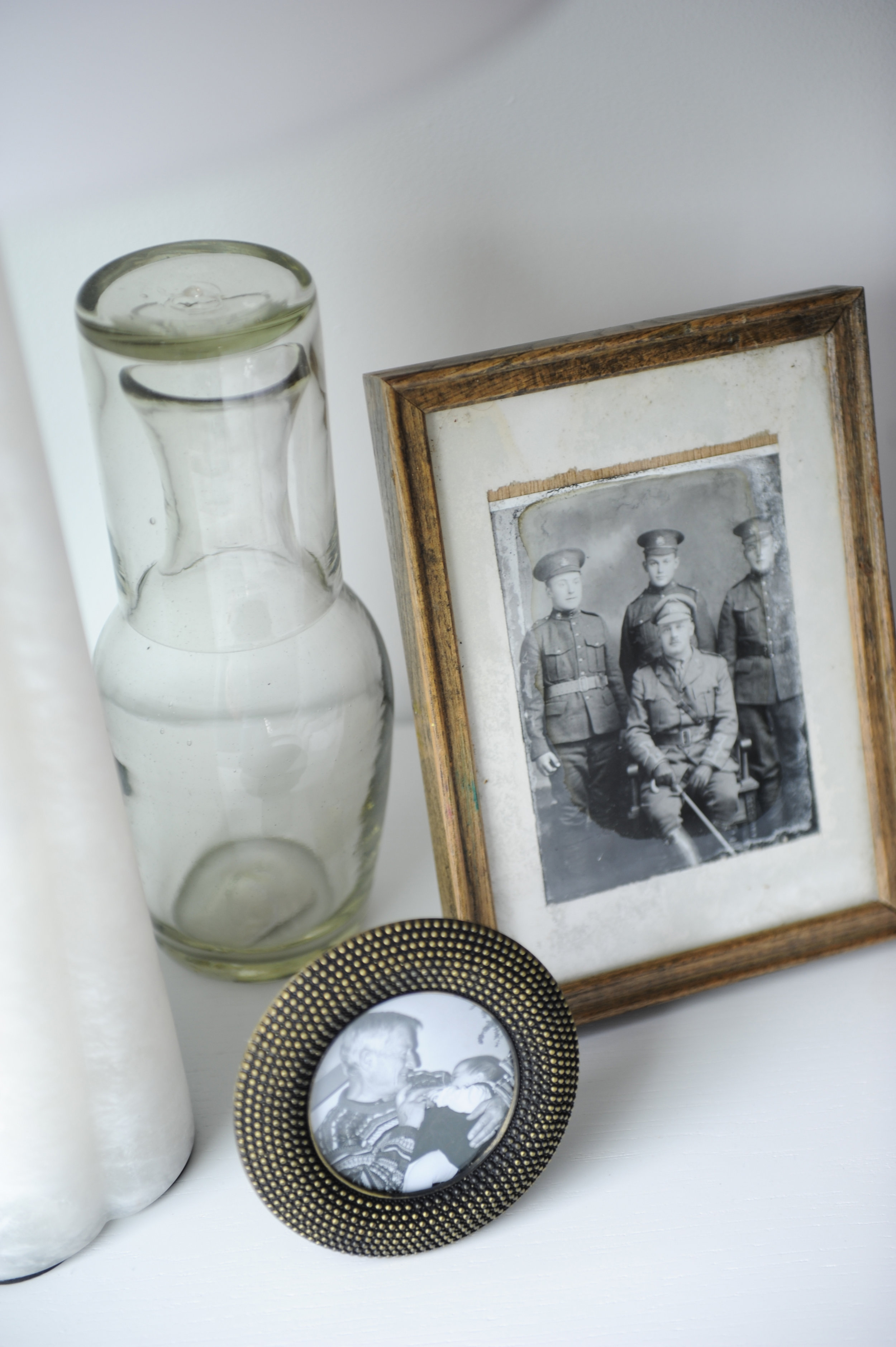 Old black and white photos sit in decorative frames next to a glass vase.