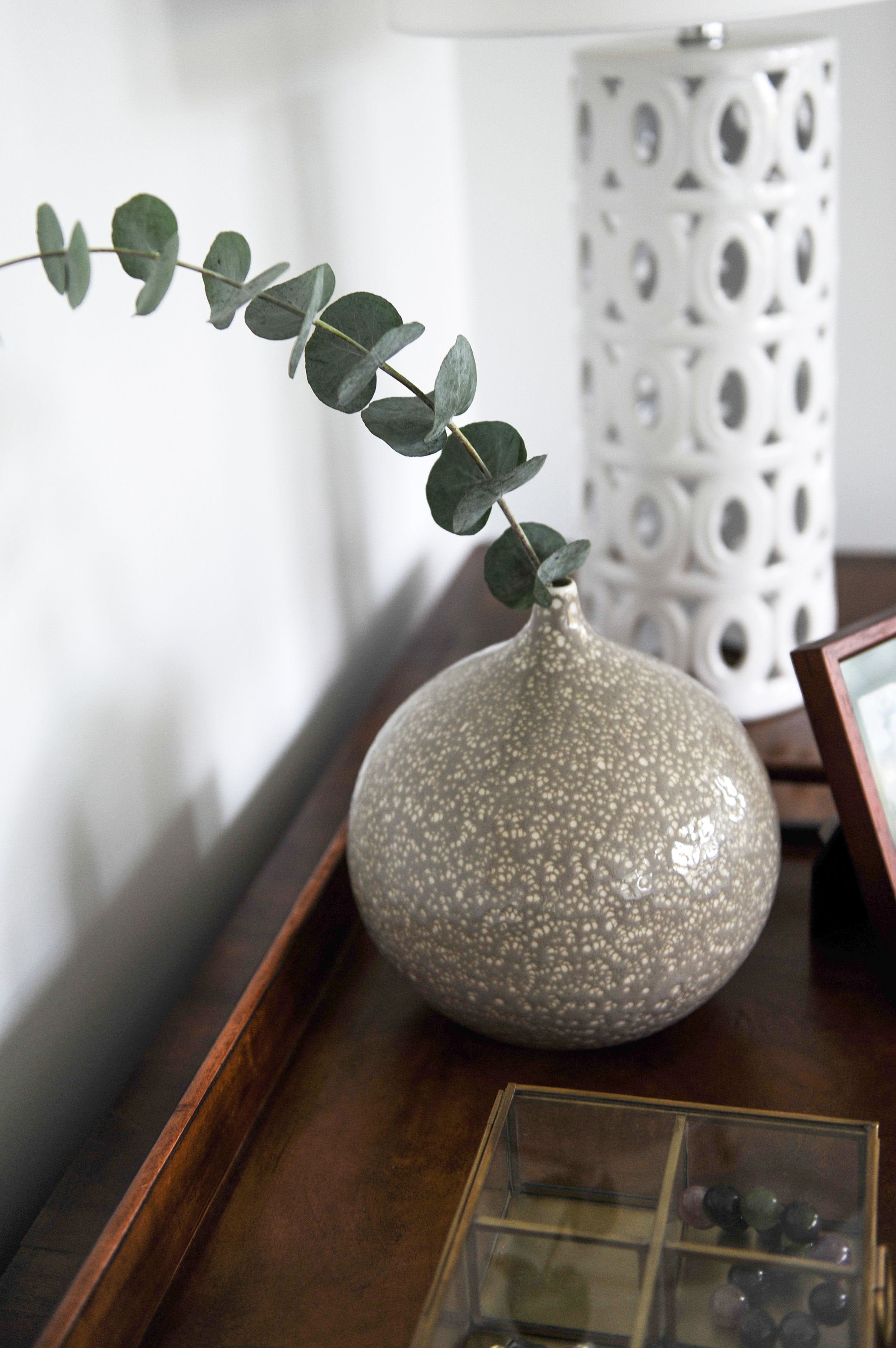 A little round vase with a decorative leaf sits in a wooden tray table beside an intricate white lamp.