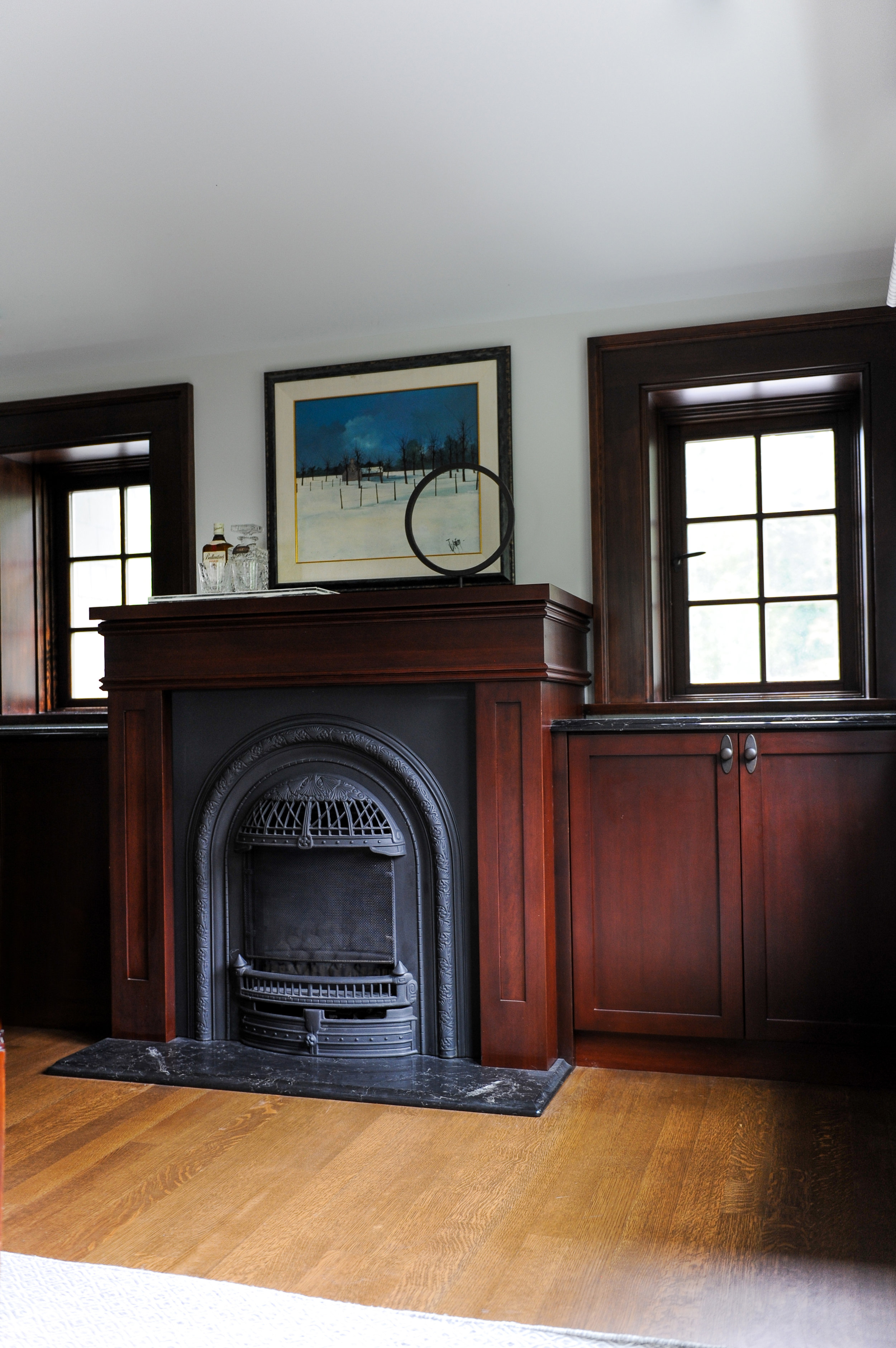 A dark iron fireplace sits inside of a dark wooden mantle and is flanked by dark wooden cabinets on either side. Above each cabinet is a six-panel window. A painting of a snowy scene hangs above the mantlepiece.