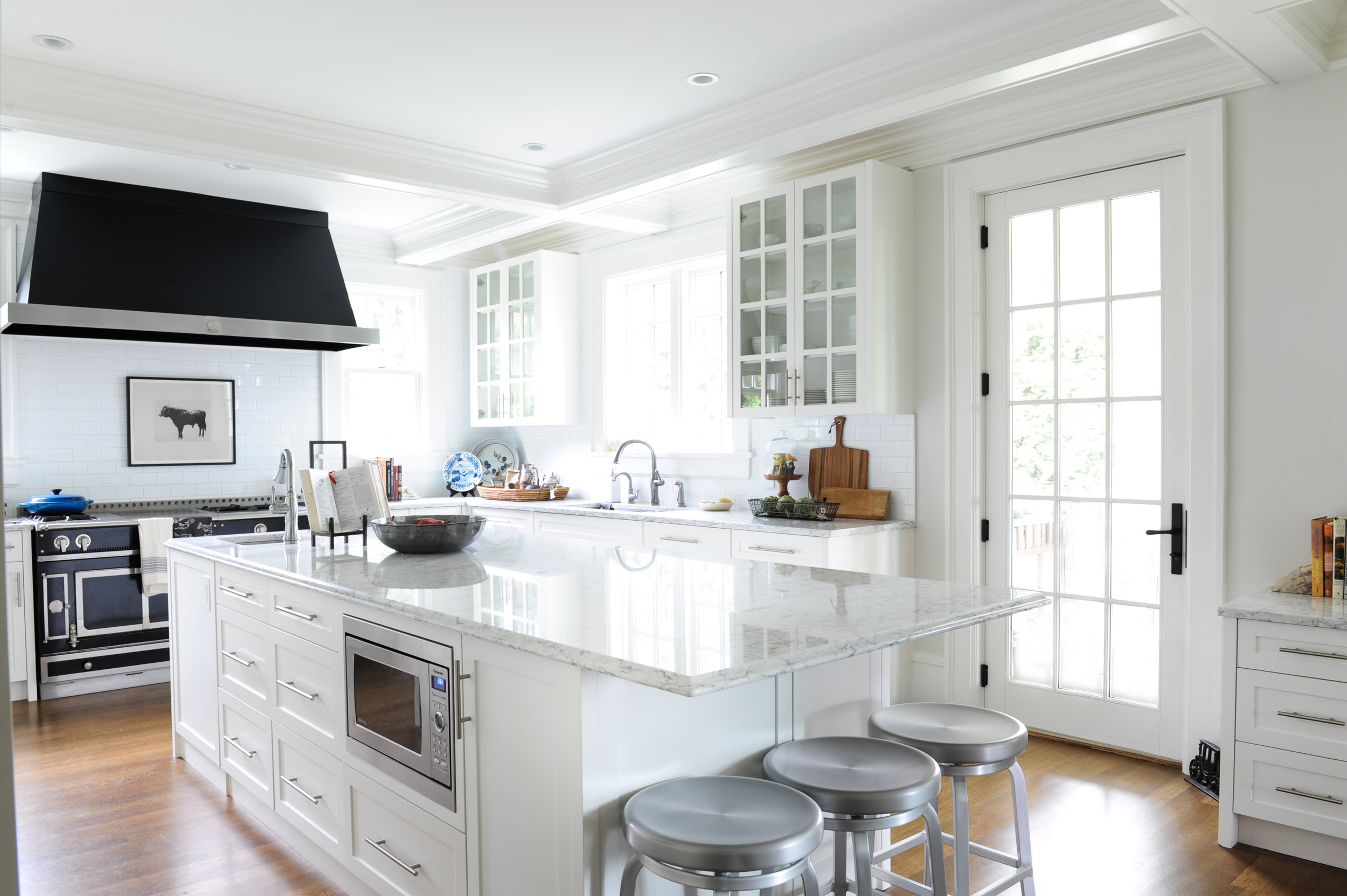 A large kitchen island with marble countertops sits in the middle of this spacious and bright kitchen. Metal bar stools are located under the end of the island and on the other end is a large antique looking stove cooktop and oven. A large matte black range hood sits above a painting of a cow, which is situated above the stove.