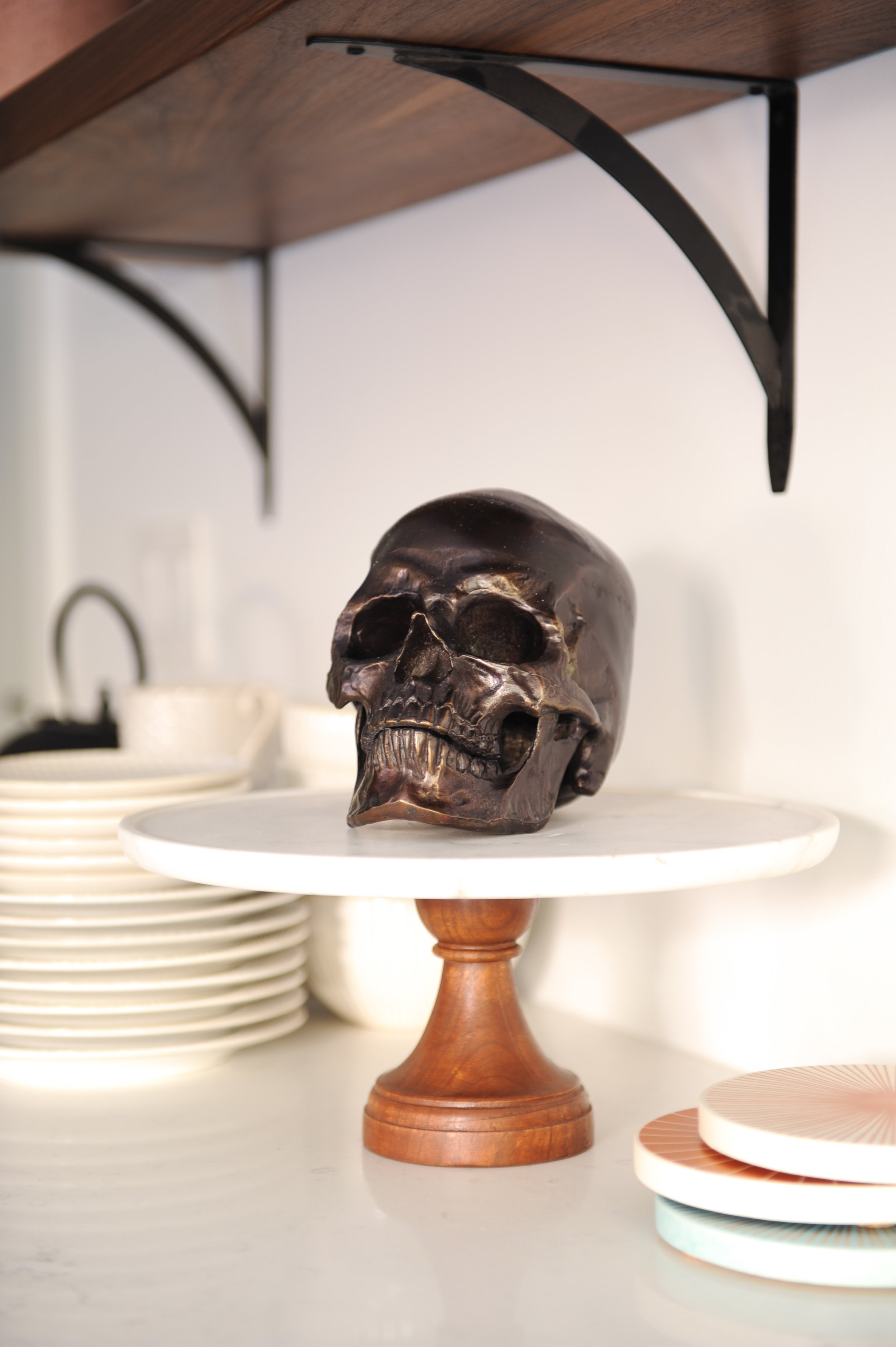 A dark metallic skull sits on a white cake stand with a wooden base.