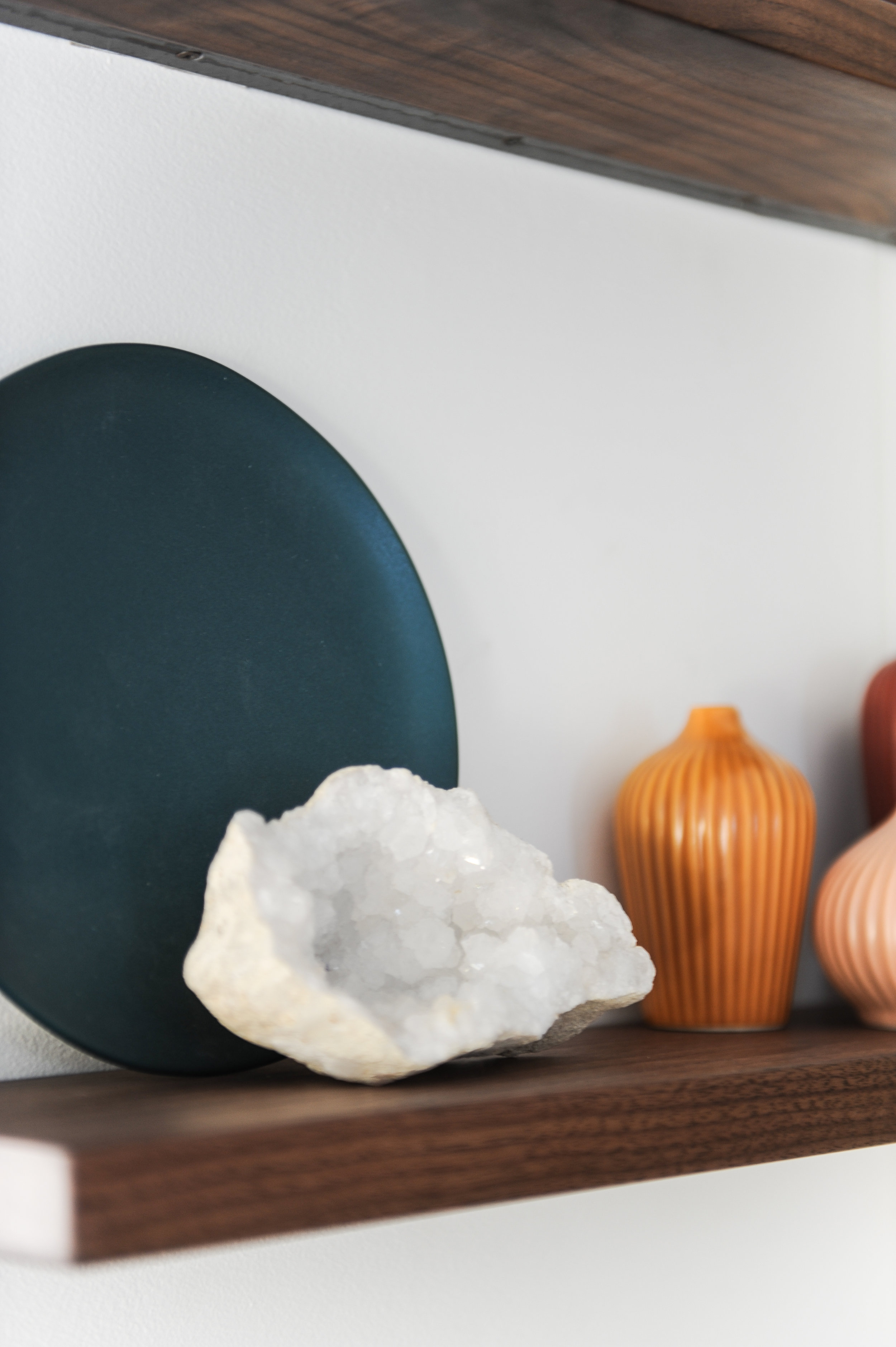 A white crystal is sitting on a wooden shelve in front of a blue vase and next to an orange vase.