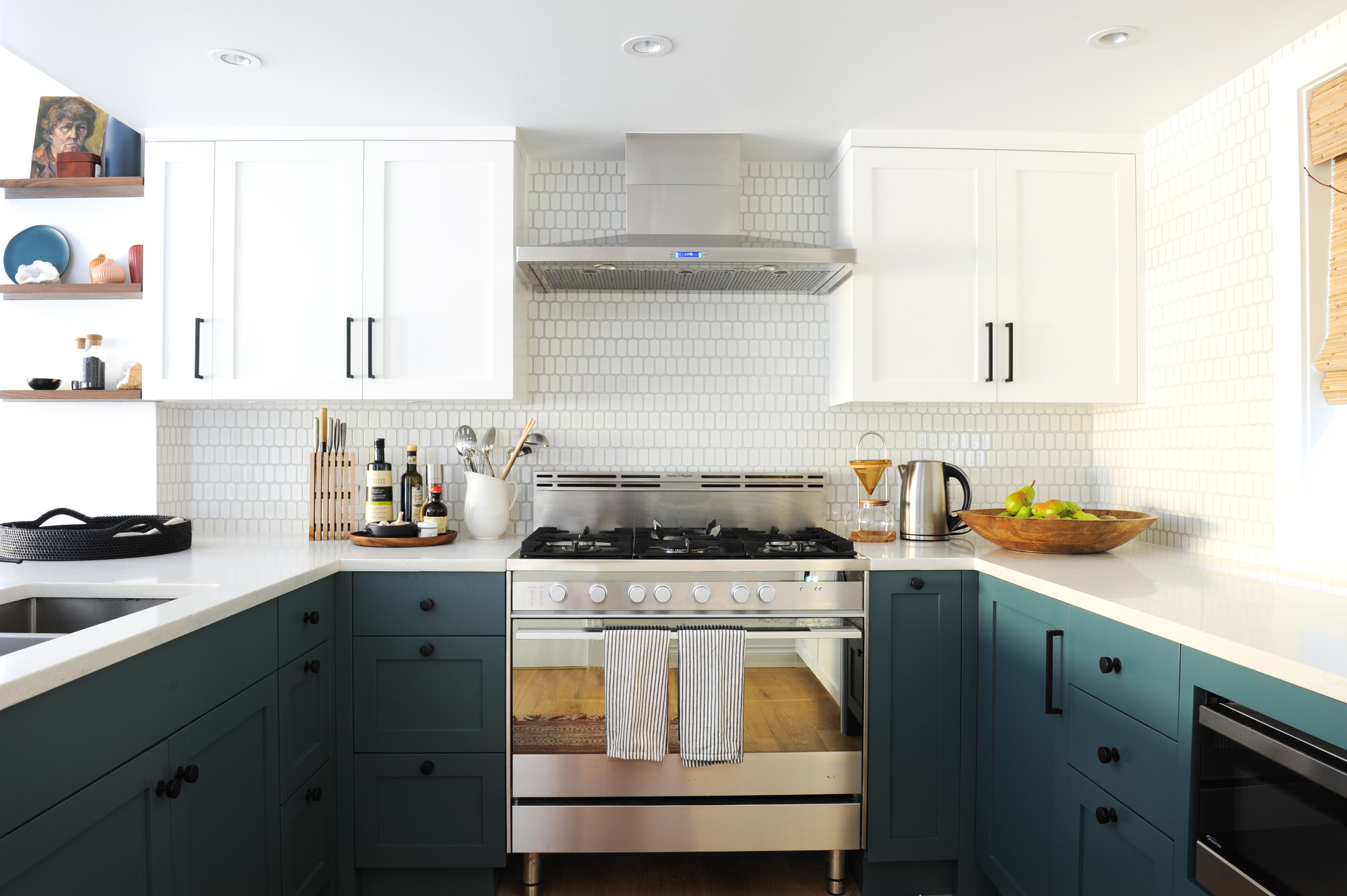 This kitchen is decorated with blue counters. A large gas stove is located in the centre and white cabinets hang on either side of the hood fan located above. The backsplash is made up of white tile.