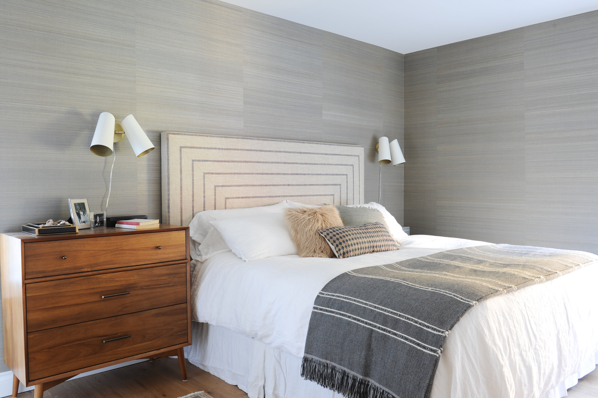 A large bed with a geometrically patterned headboard sits next to a dark wood bedside table dresser drawer. The walls are made up of beige panels. Above each bedside table sits two wall sconces.