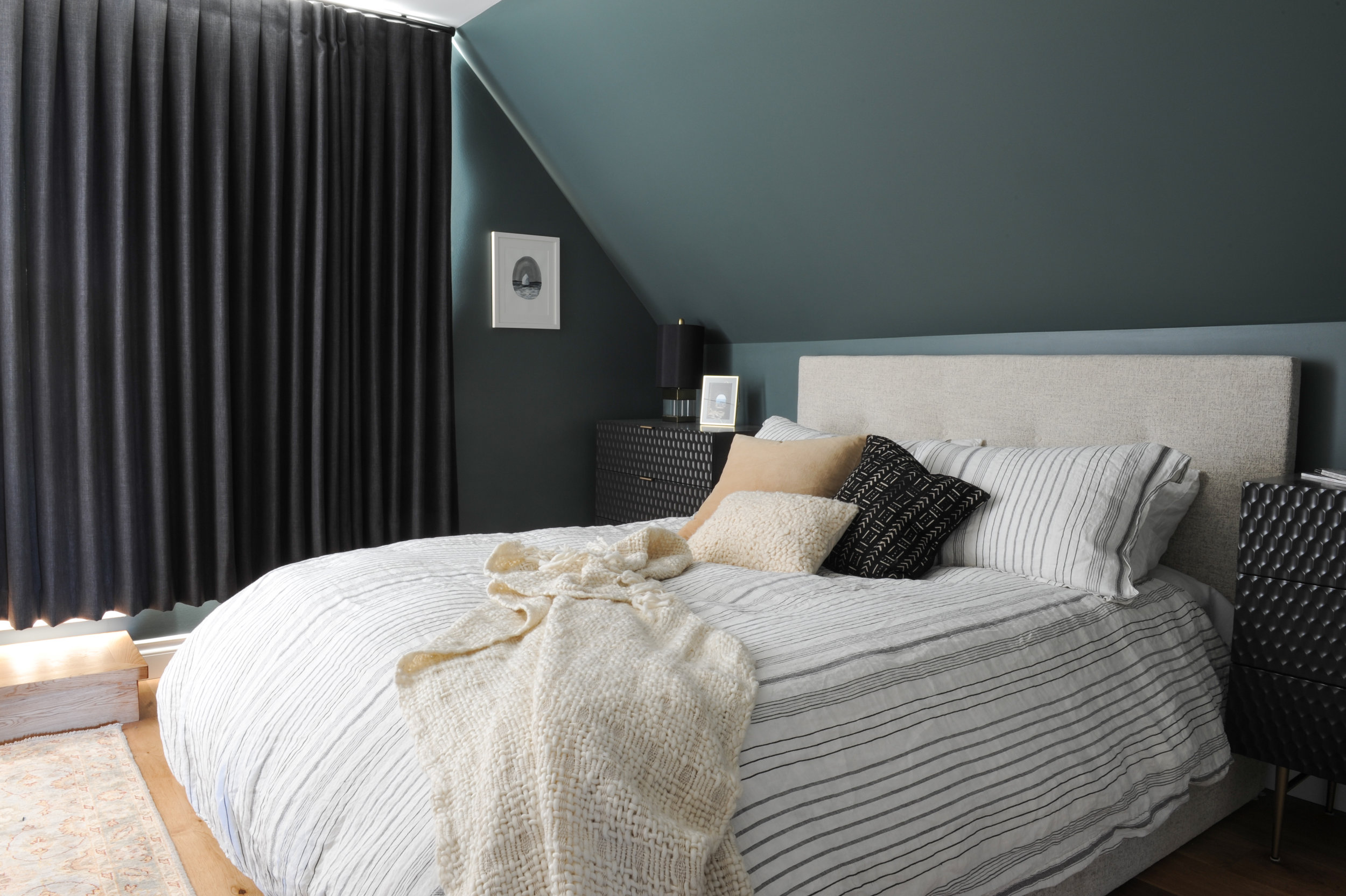 This bedroom has dark teal walls and blackout curtains for a dramatic effect. The bed has a beige headboard and sits next to a black textured night stand dresser.