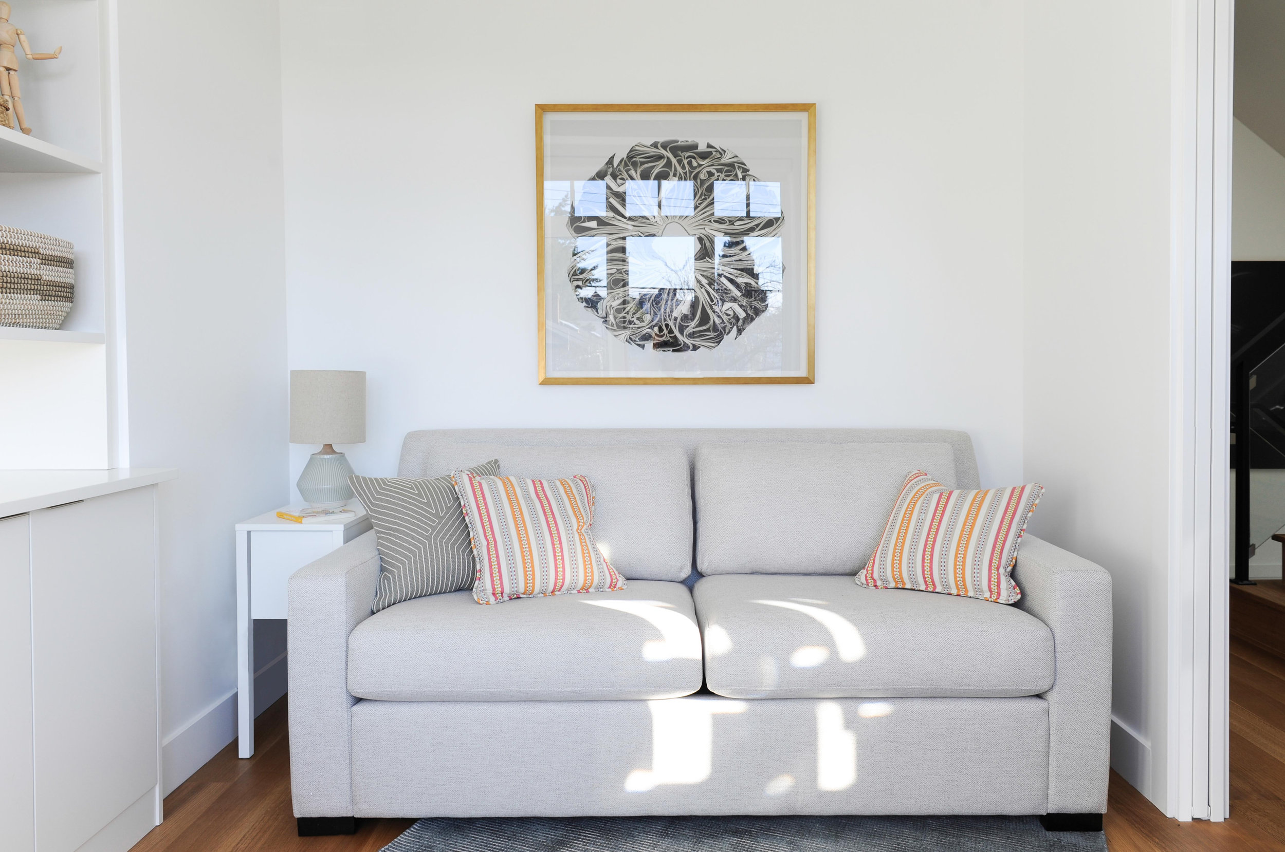 A grey couch and small end table sit in a large alcove and a black and white painting in a brown frame hang above it.