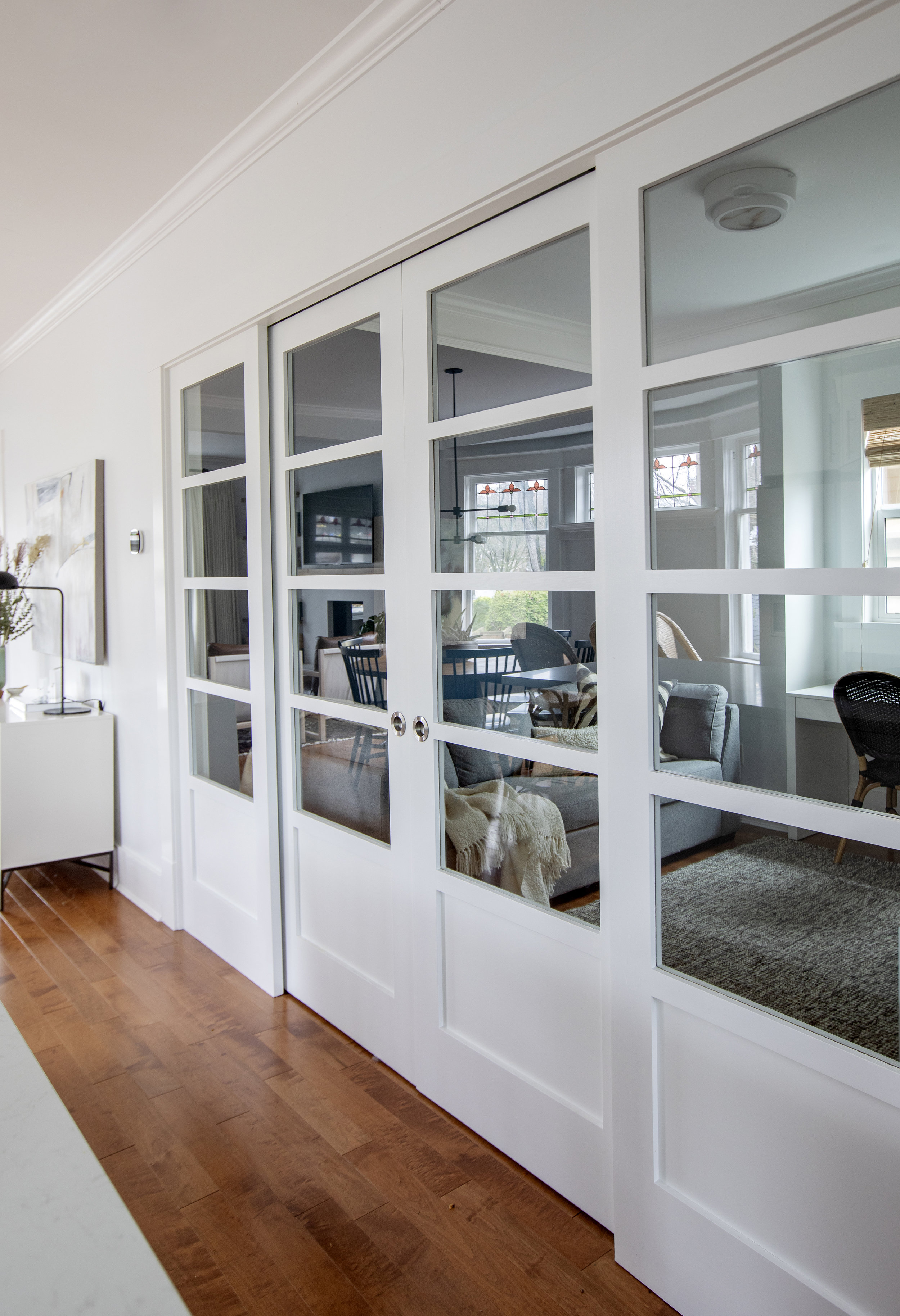 Large, glassed double doors separate the kitchen and the living room from the family room. The living room is reflected clearly in the glass.