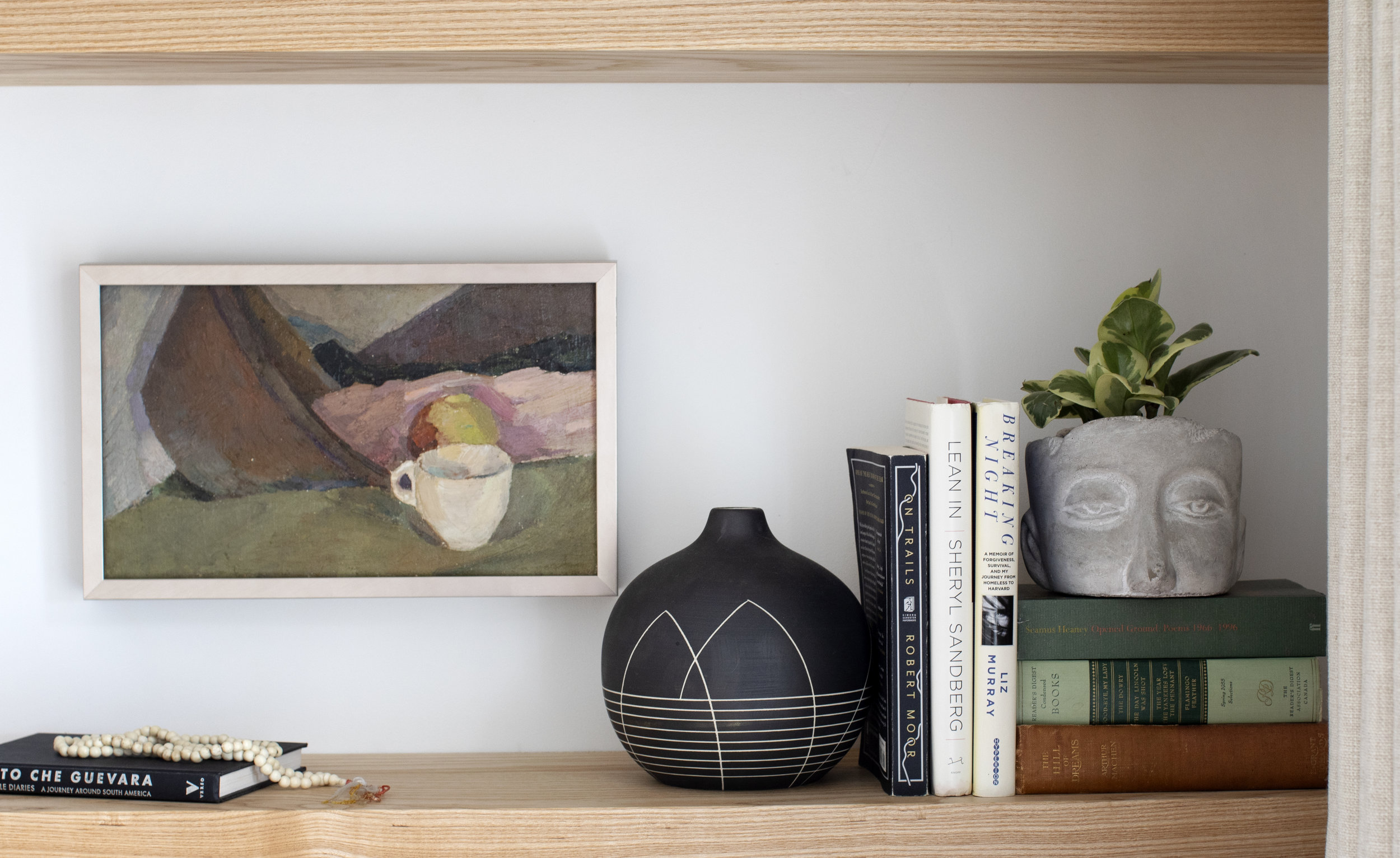 A shelf in the living room displaying a vase shaped like a face, a black decorative jar, some books and a painting of a coffee cup