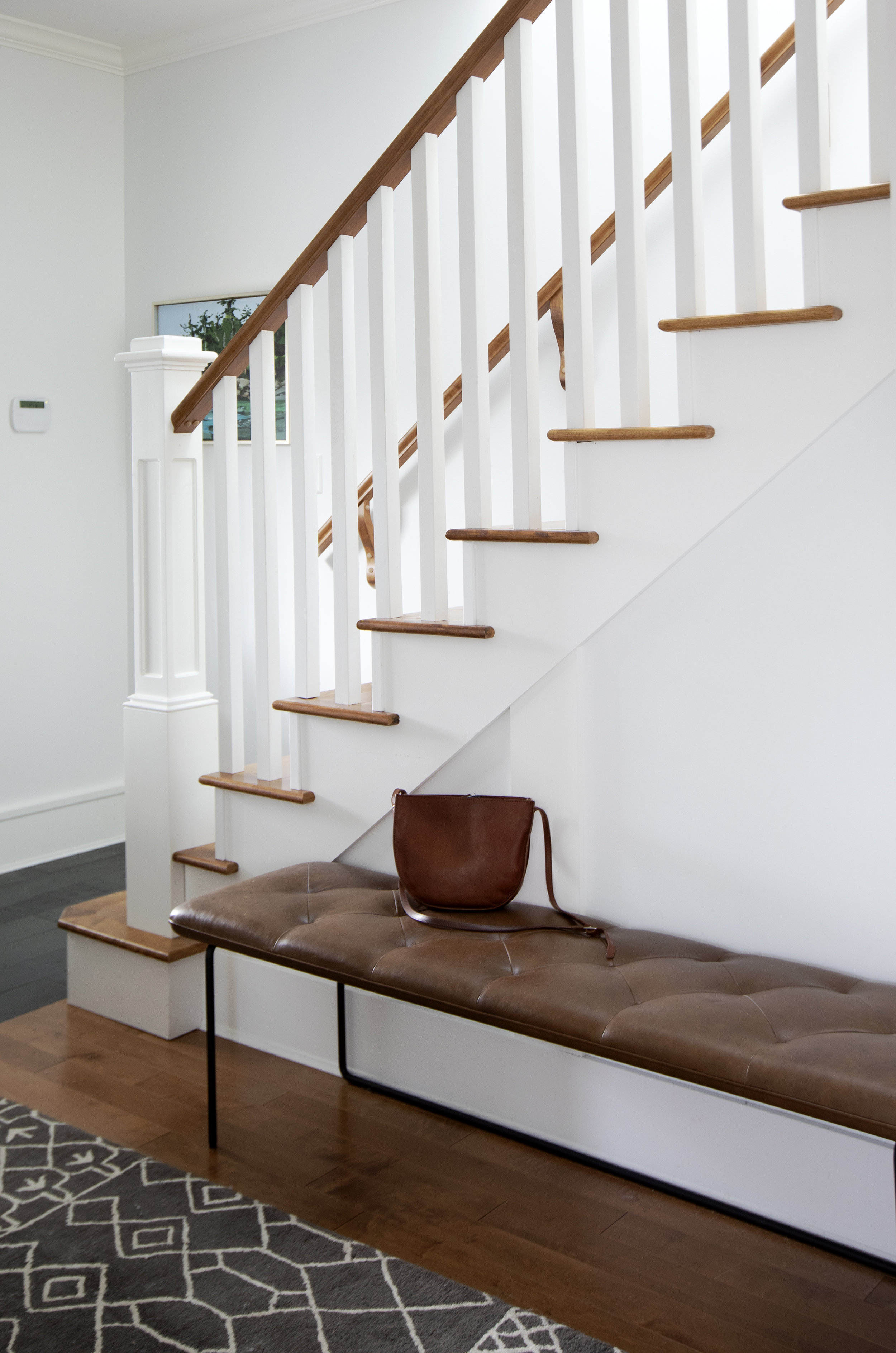 A large leather bench sits below the white and wooden staircase.