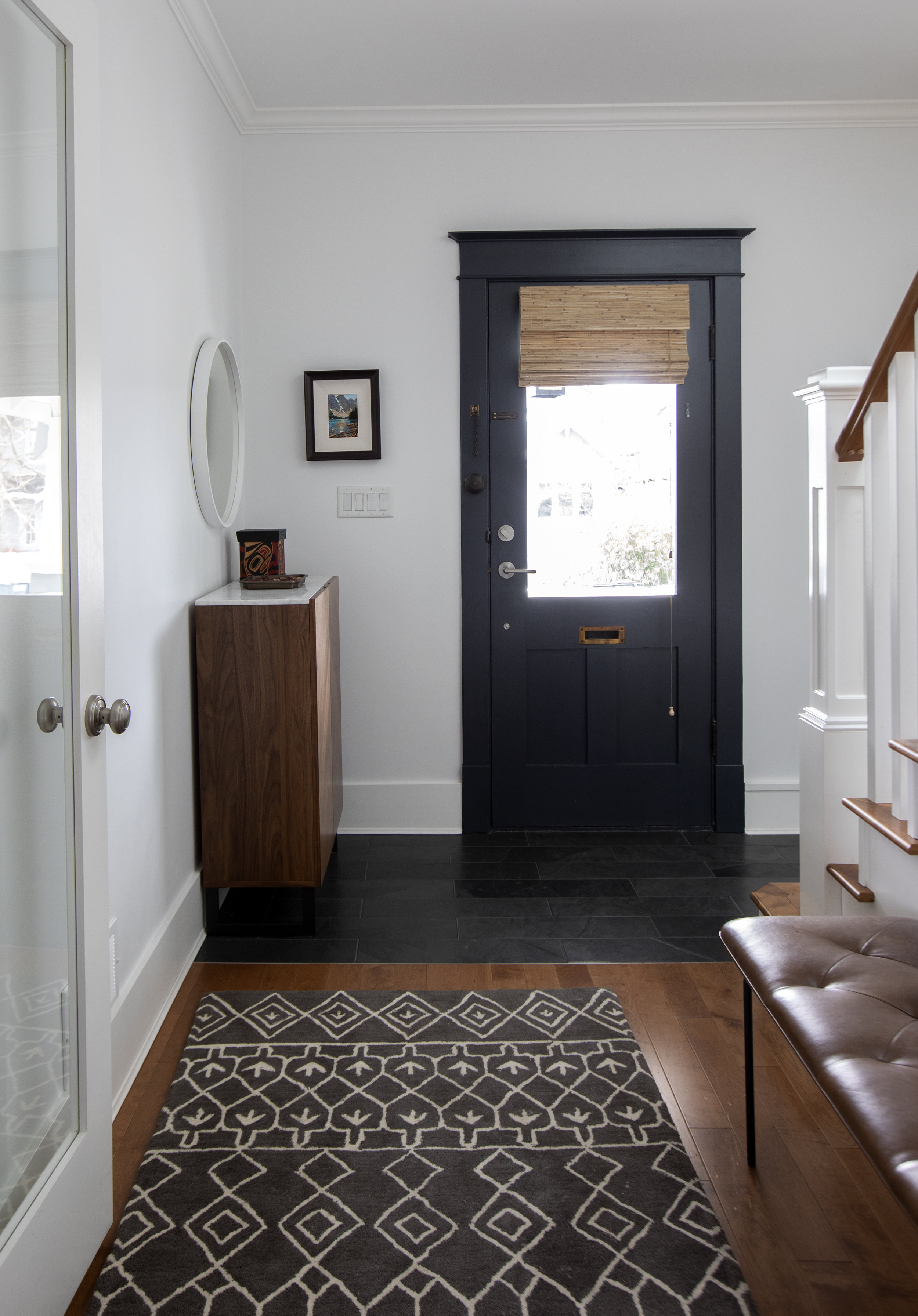 The front hallway of this house, a geometric floor runner leads to the front door, which is painted black. To the left is a darker wooden dresser with a white top, and hanging above that is a decorative white mirror