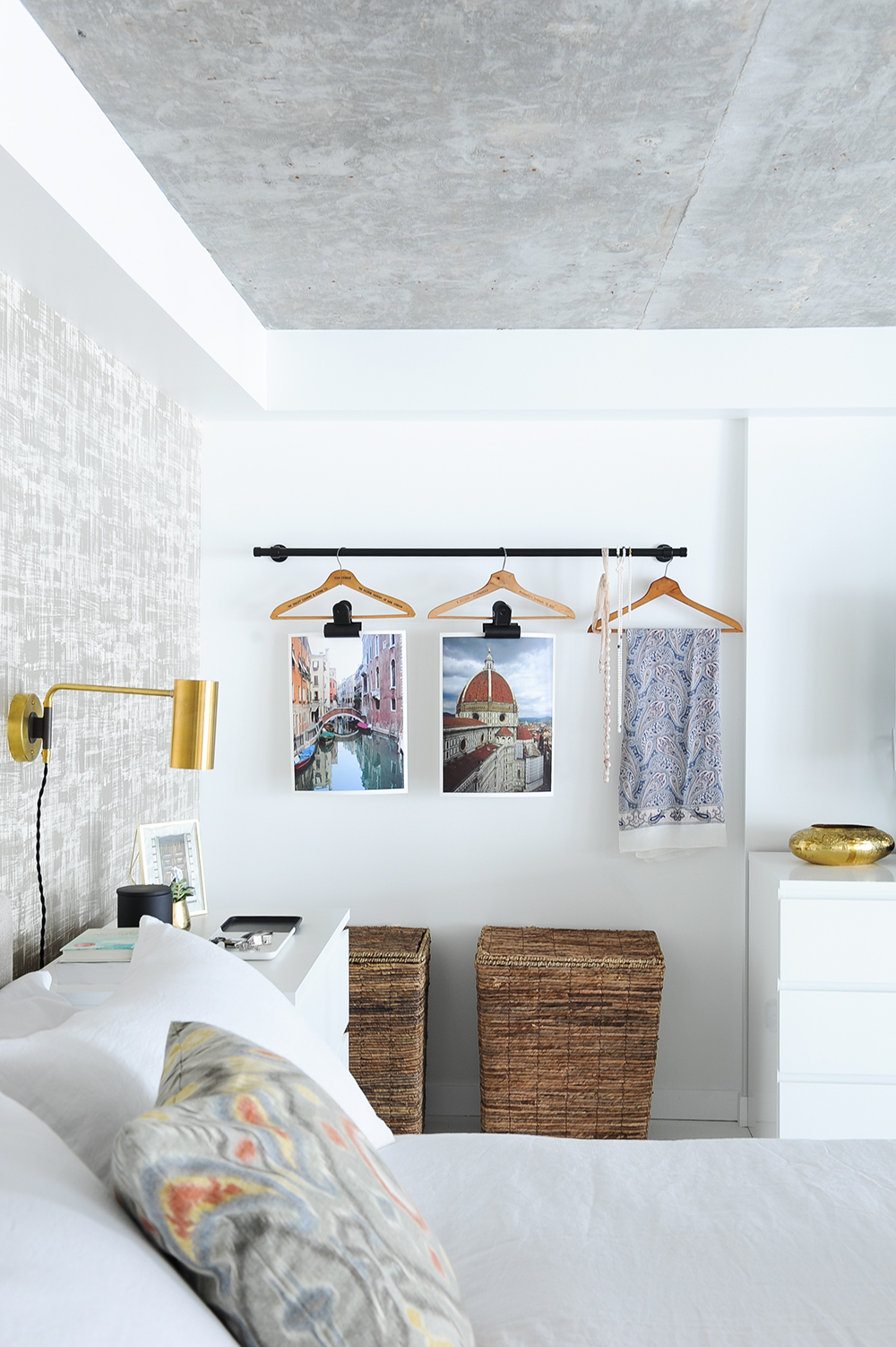 Wooden laundry baskets and decor, such as two paintings, a scarf and jewelry hanging on a black iron curtain rod in a bedroom,