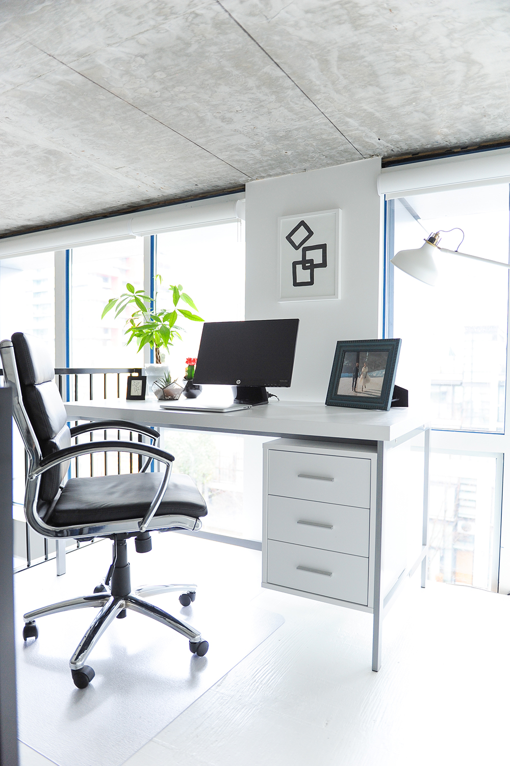A bright office space with a grey and white table with a computer and framed photo sat on top of it, with a white filing cabinet attached to the base of the desk and a black desk chair