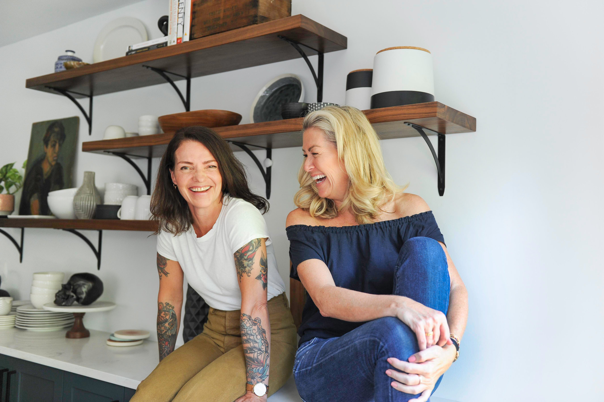 Greer & Jamie are sitting in the kitchen on white countertops in front of an array of wooden shelving with various decor, such as ceramic jars, cups and a wooden bowl. Greer is facing the camera while Jamie is looking to her right and they are both laughing.