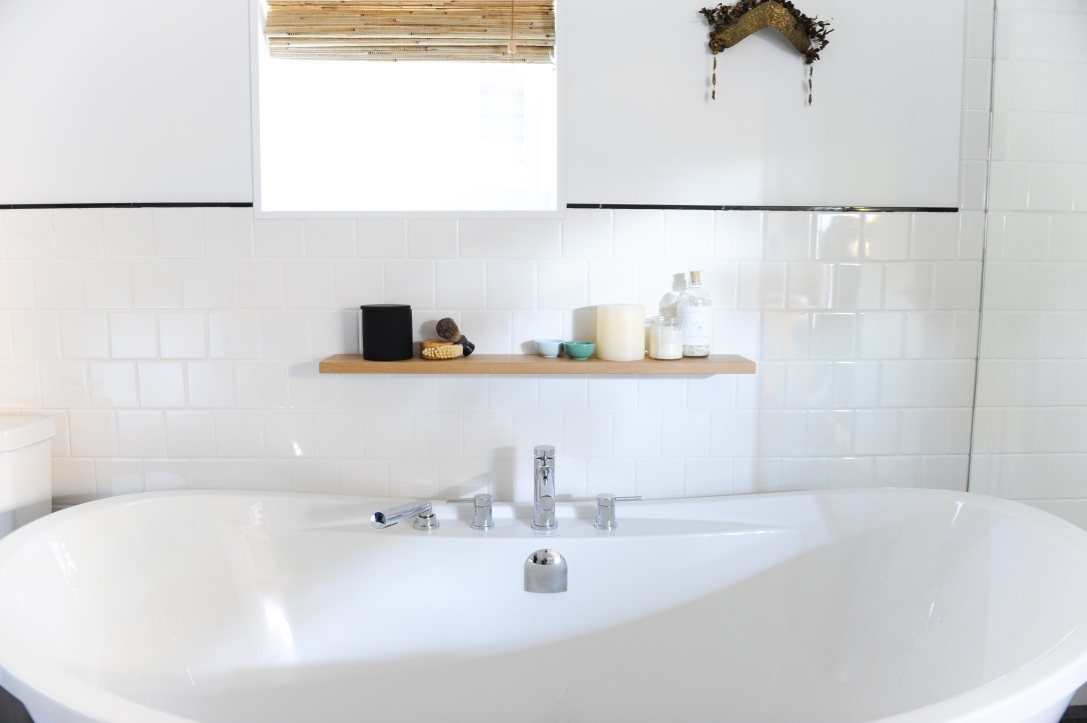 The soaker tub has a wooden shelf built into the wall above it, where various relaxing products sit, such as candles and salt scrubs. An open window sits above the shelf, with the wooden blinds pulled up to let light in.
