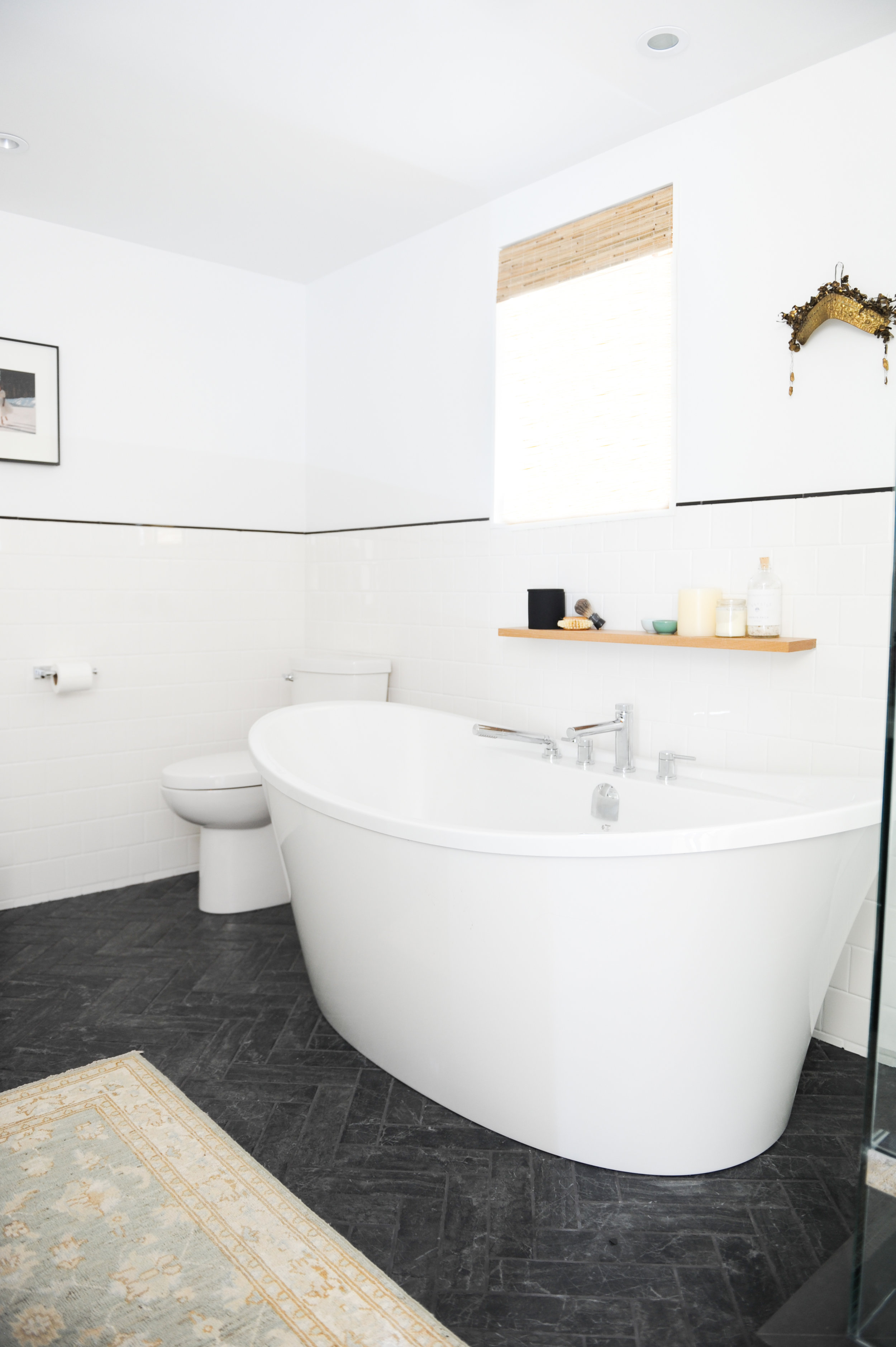 A large, luxurious soaker tub sits in the centre of this white tiled bathroom, on top of beautiful black tiled floors.