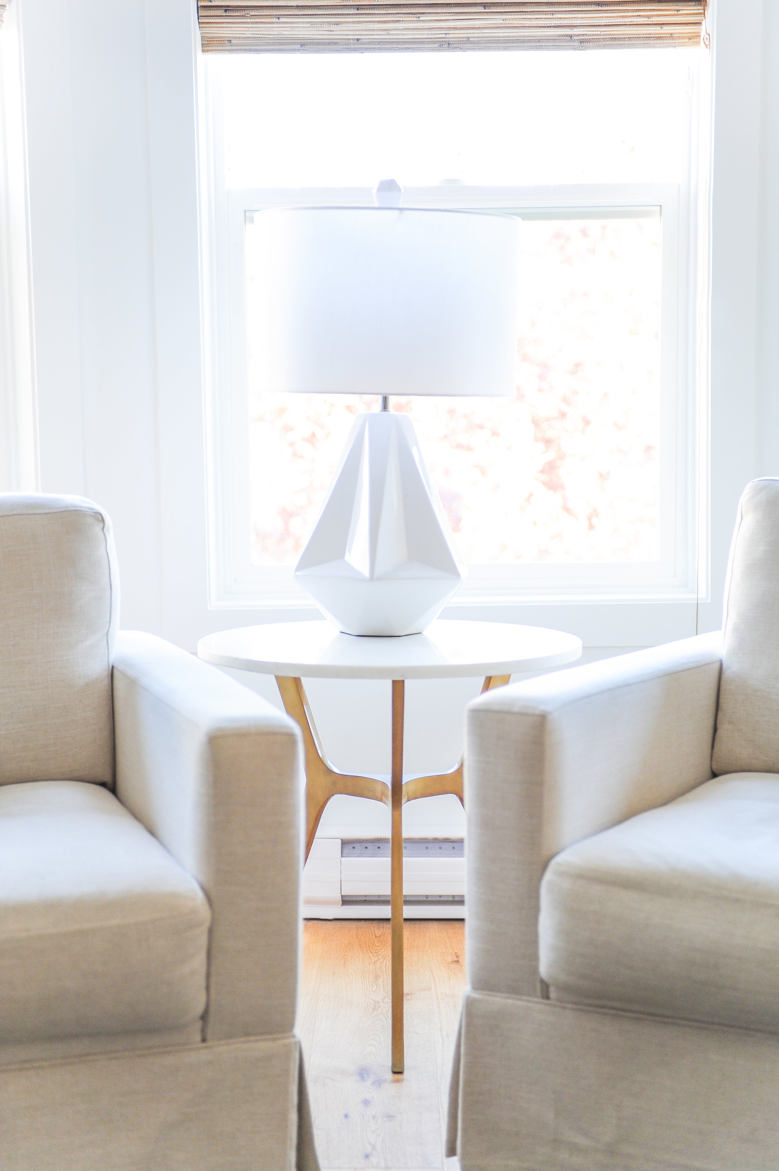 A white geometric lamp on a wooden end table with white table top between two cream coloured armchairs.