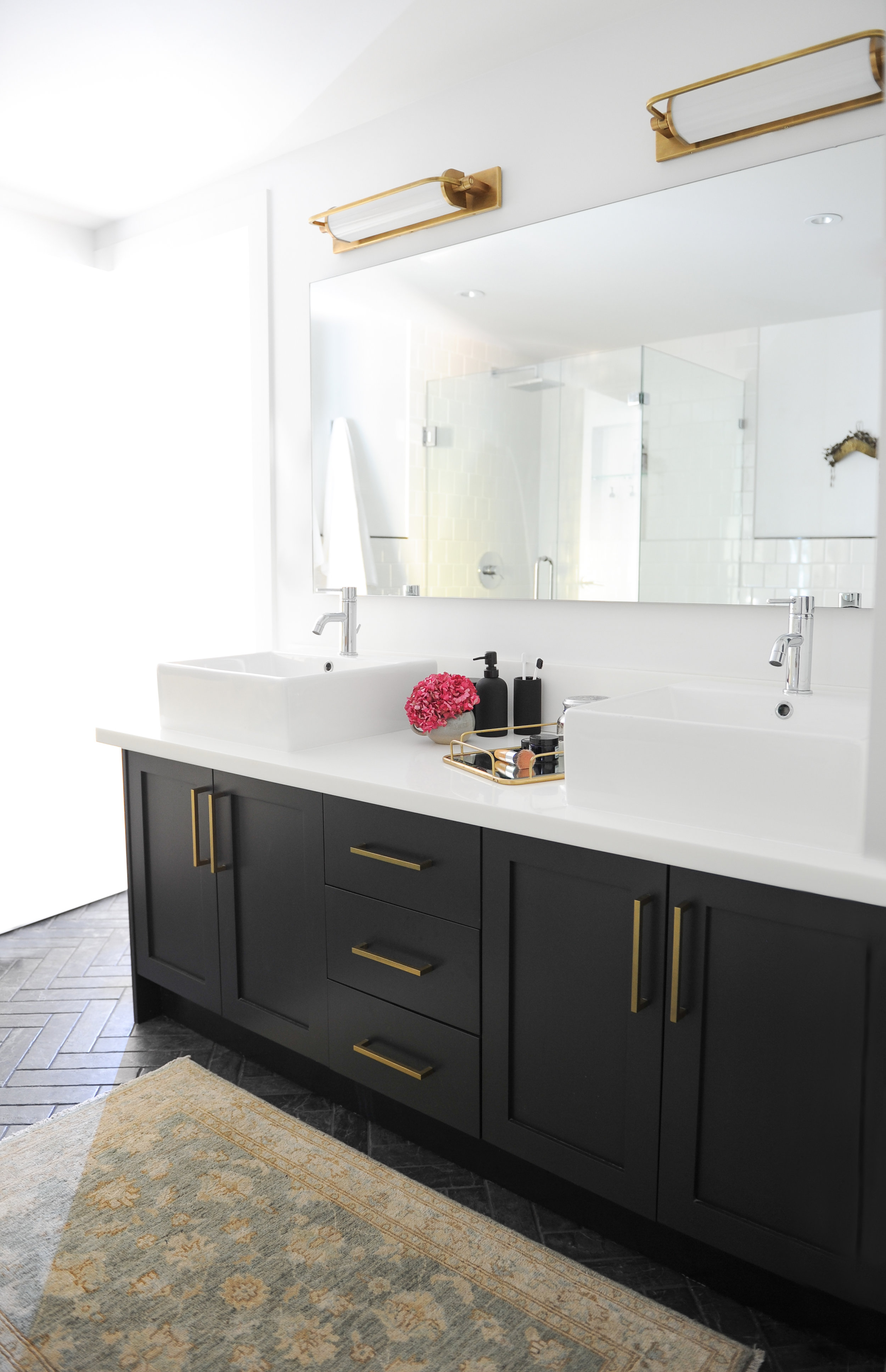 This bright bathroom is decorated with black counters with white tops. There are his and her sinks with gold light fixtures above the long mirror.