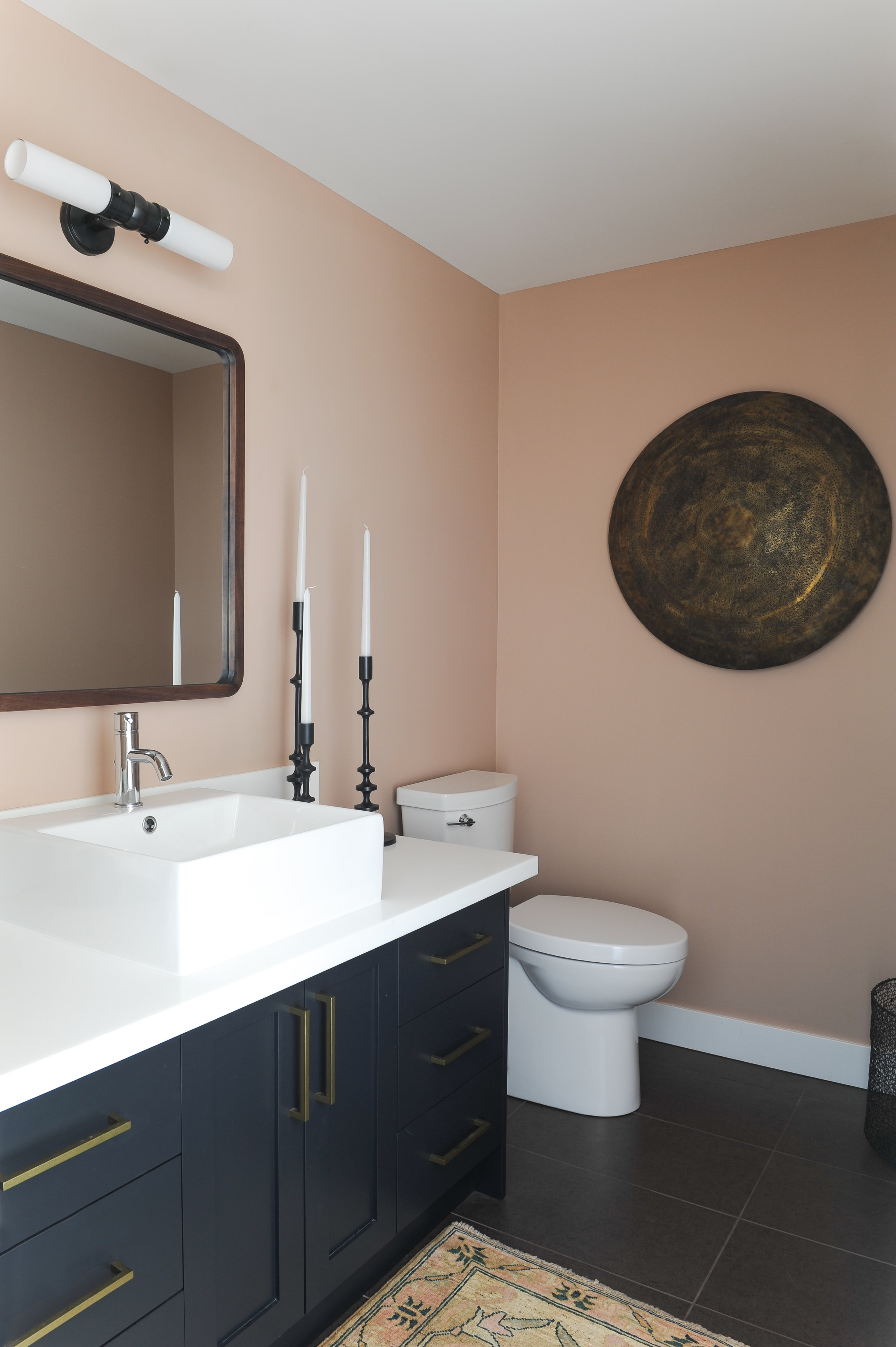 A pink walled bathroom is balanced by the black counters and large decorative metal shield that hangs on the wall above the toilet.