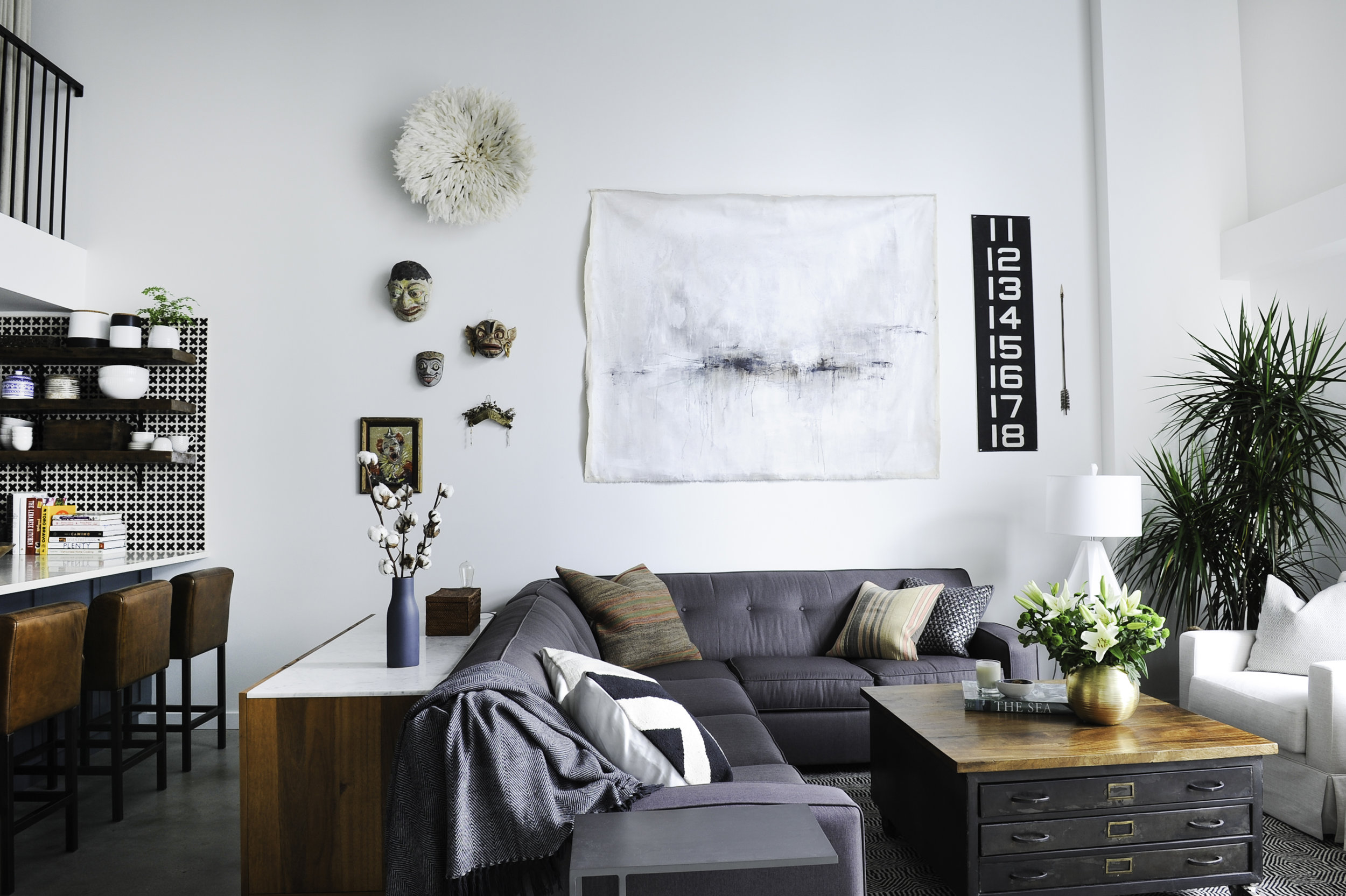 A sunny living room with a wooden coffee table surrounded by a large grey sectional and white armchair, with various eclectic decor on the walls, including masks, a various art prints.