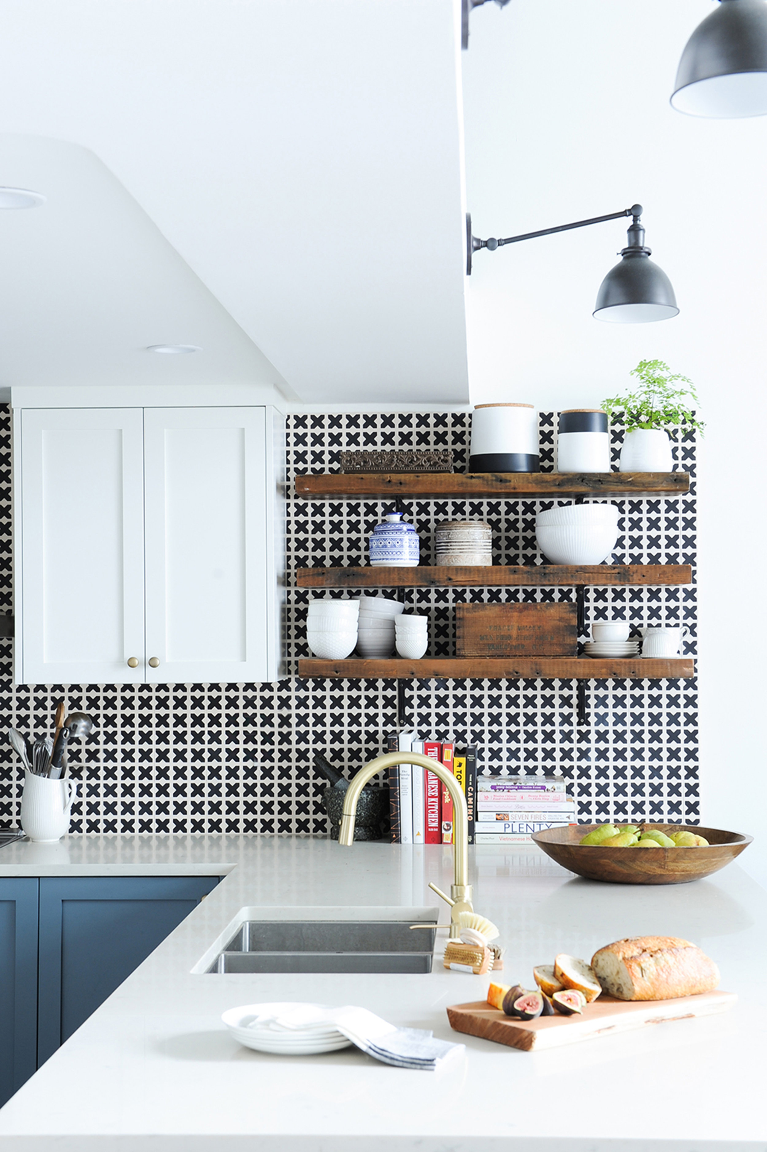 A sunlit kitchen counter and wooden shelves on a black and white patterned tiled wall, complete with various kitchen items, including bowls and ceramic jars on the shelves, and a wooden bowl of fruit and a wooden plank with bread and figs sitting on the counter.