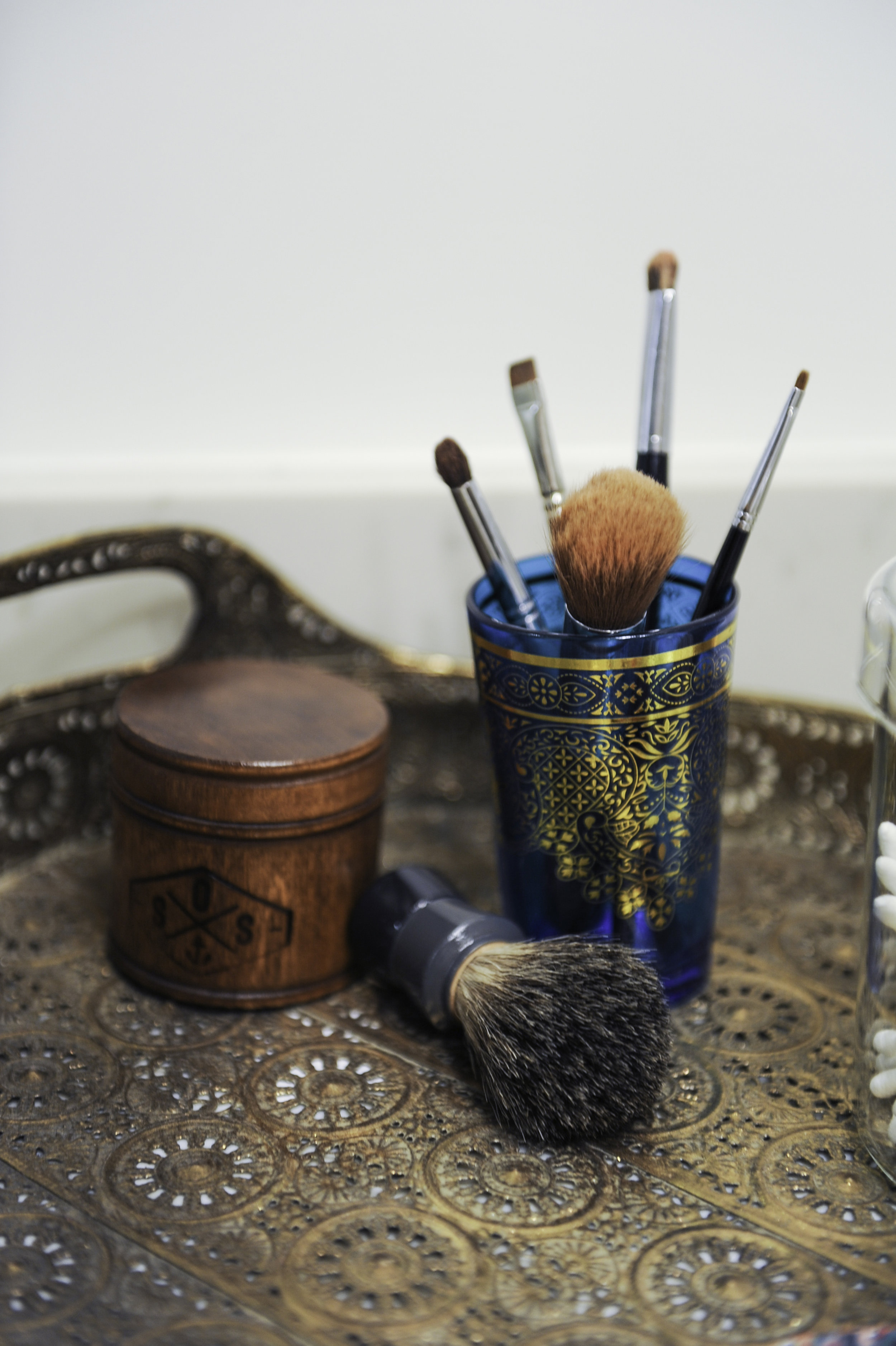 Cosmetic brushes inside a gold detailed blue glass cup and men's shaving products sit inside a decorative wooden tray.