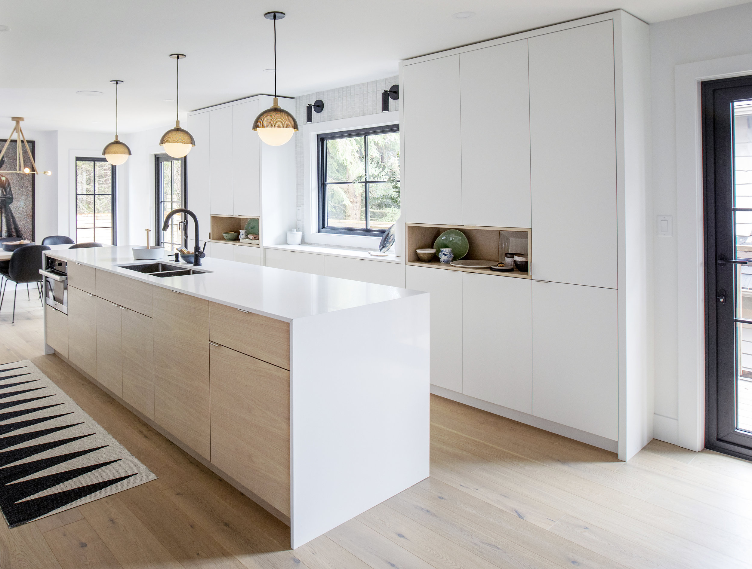 Kitchen area at Alderfield Place; modern countertops and beautiful light fixtures hang above the kitchen island.