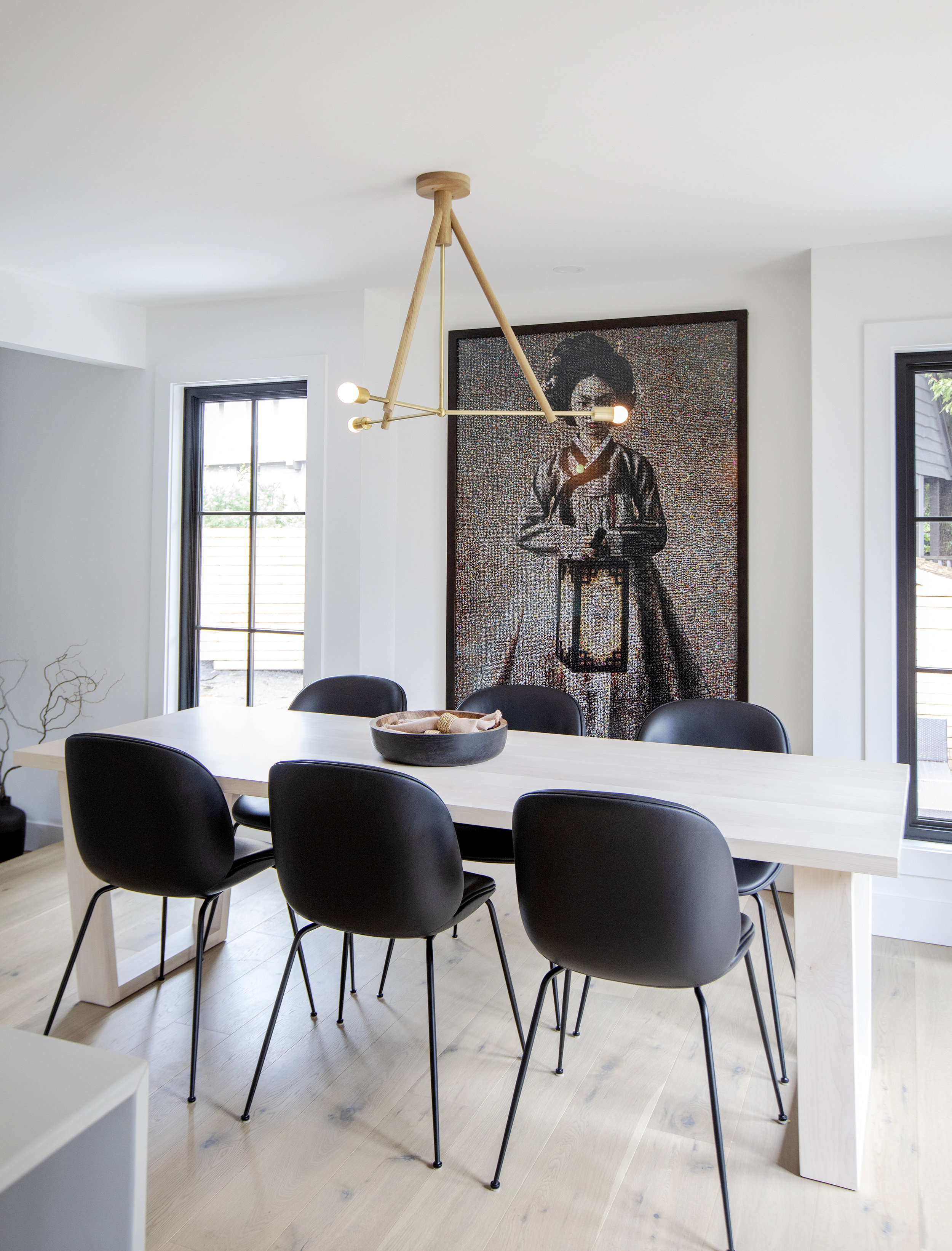 Dining room at Alderfield Place; white dining table surrounded by black dining chairs, a painting of a Japanese woman hangs behind.