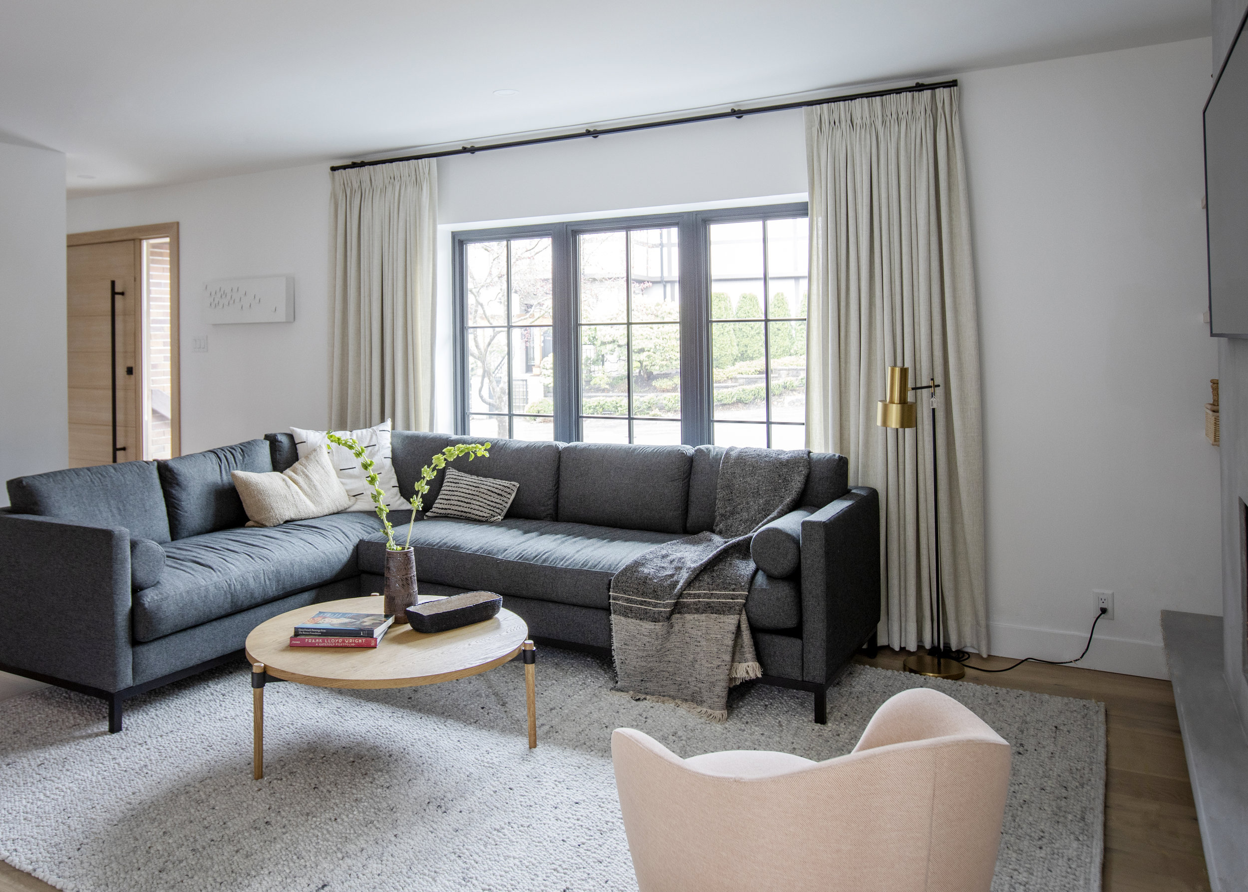 The modern and chic living room at Alderfield place, with L shaped couch and white accent armchair.