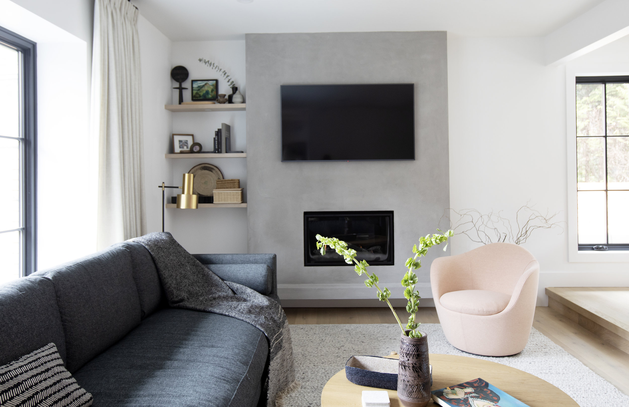 The TV sits above the inset fireplace at Alderfield place. A beautiful bookshelf with various knick knacks sits beside it.