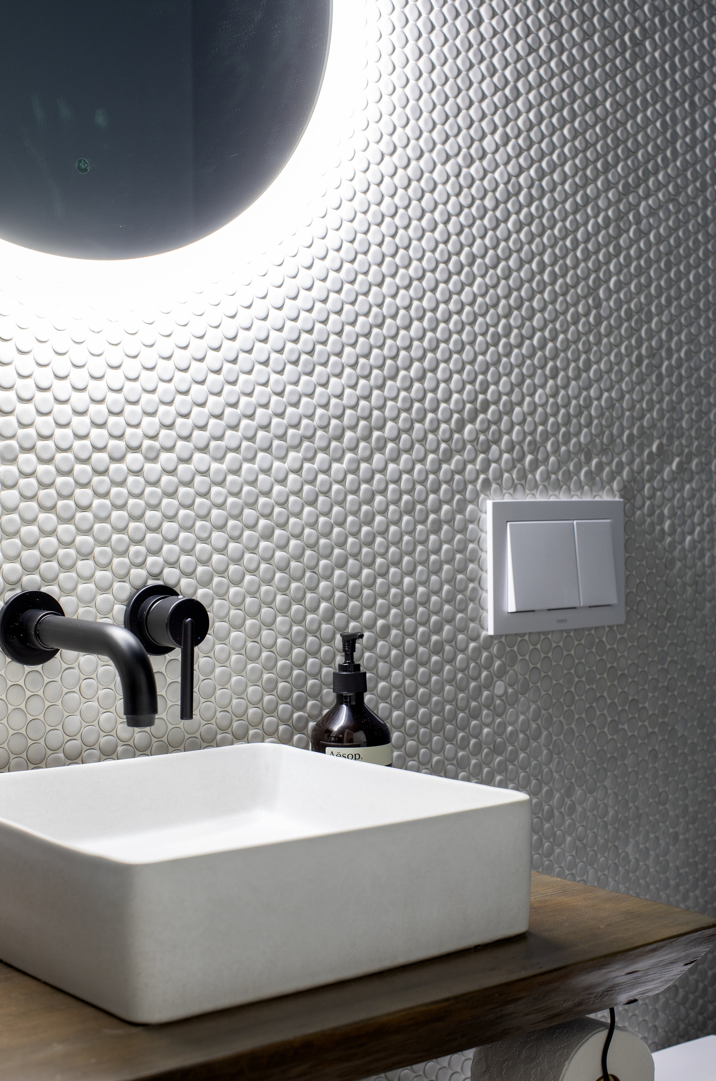 A bathroom at Alderfield Place, with white textured walls and a vanity mirror where light comes from behind.