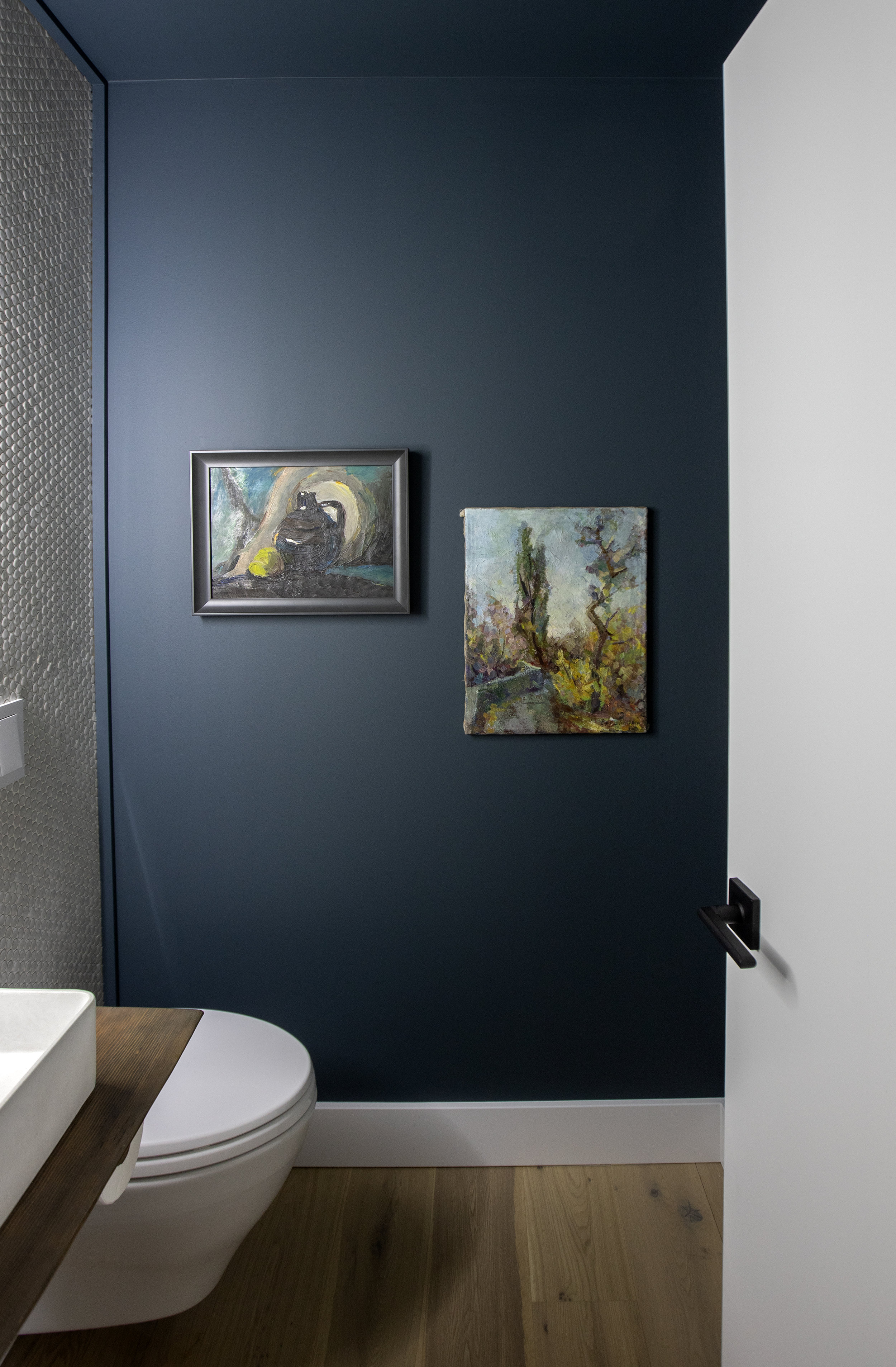 The bathroom at Alderfield place has a navy blue accent wall with two antique paintings resting above the toilet.
