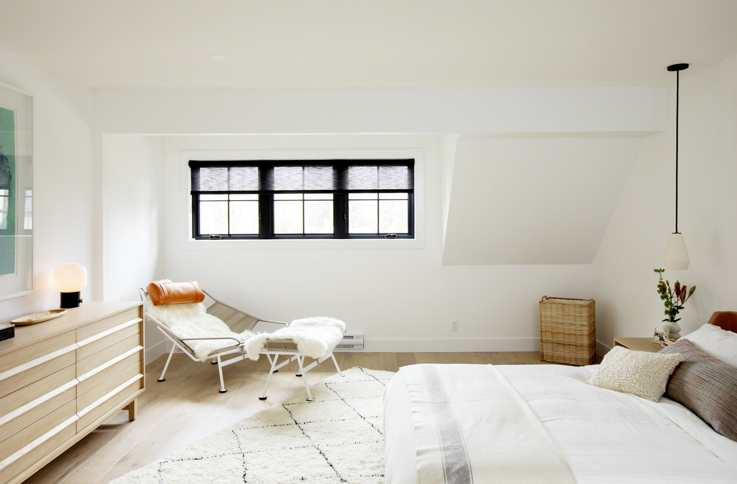 The bedroom at Alderfield Place is bright and cheerful. A lounge chair sits in the corner in front of the low bed.