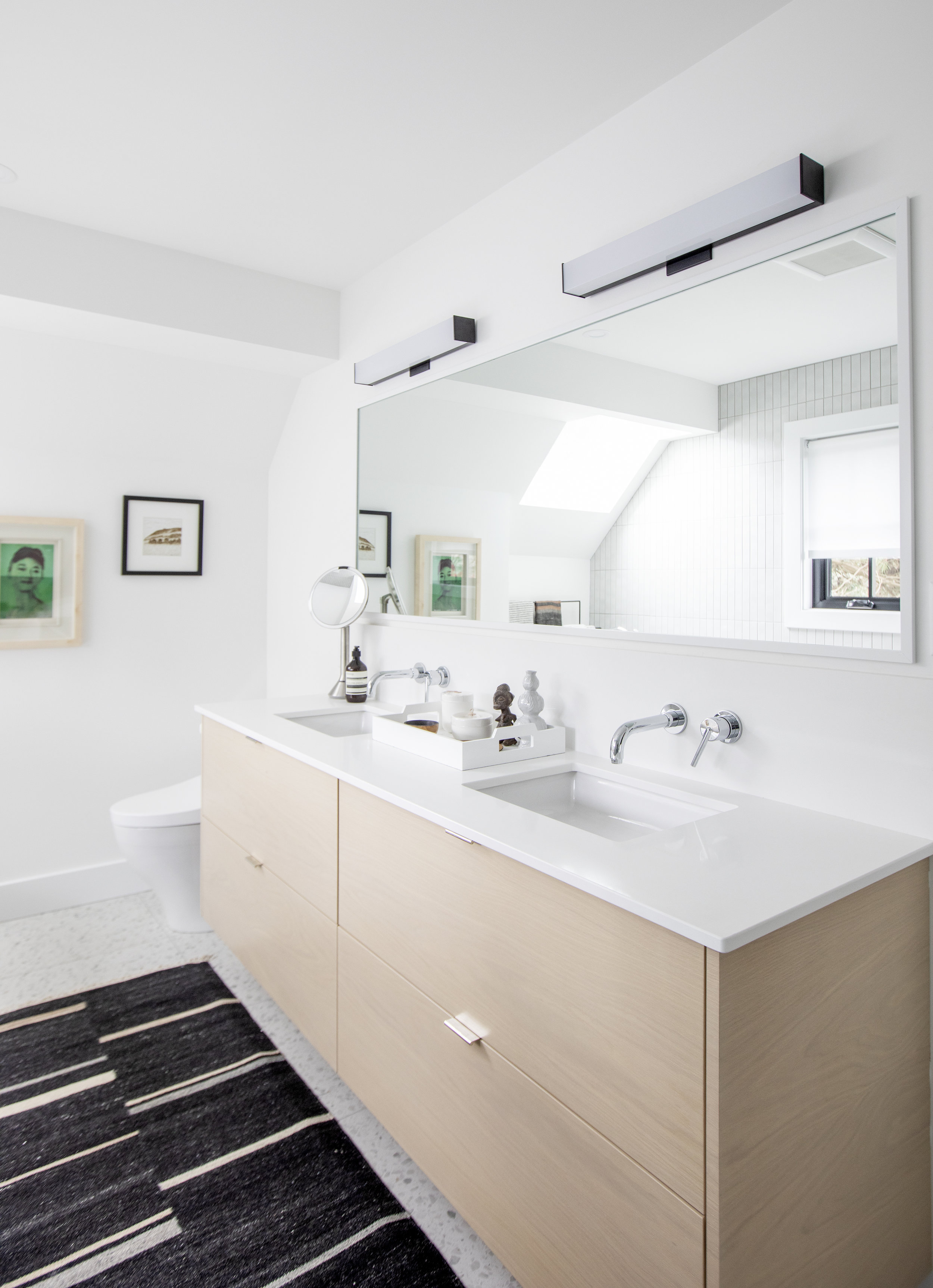 The his and hers sinks in the master bathroom sit below a large rectangular mirror in Alderfield Place