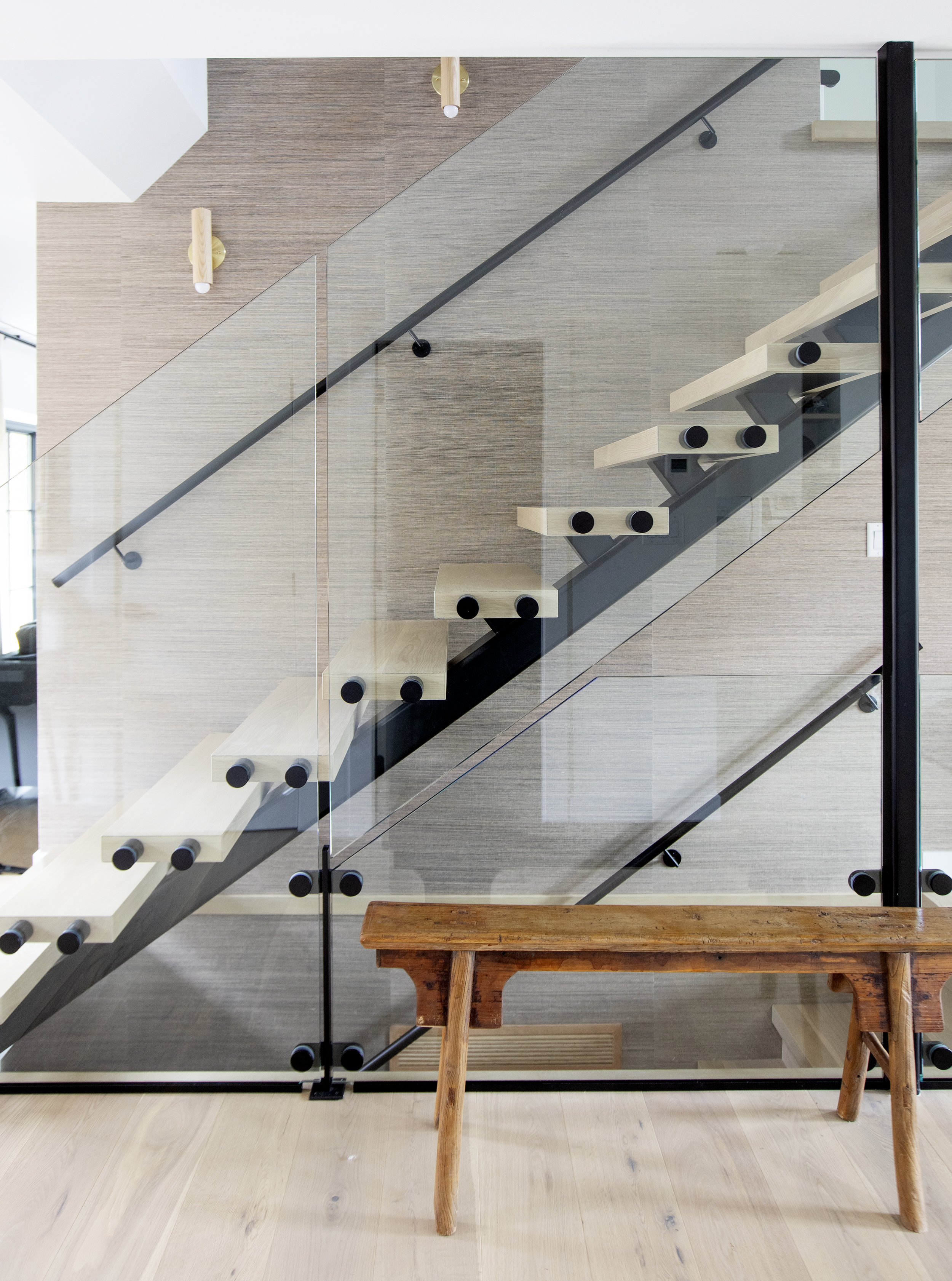 A look of the modern staircase in Alderfield Place, featuring glass railings and floating steps.