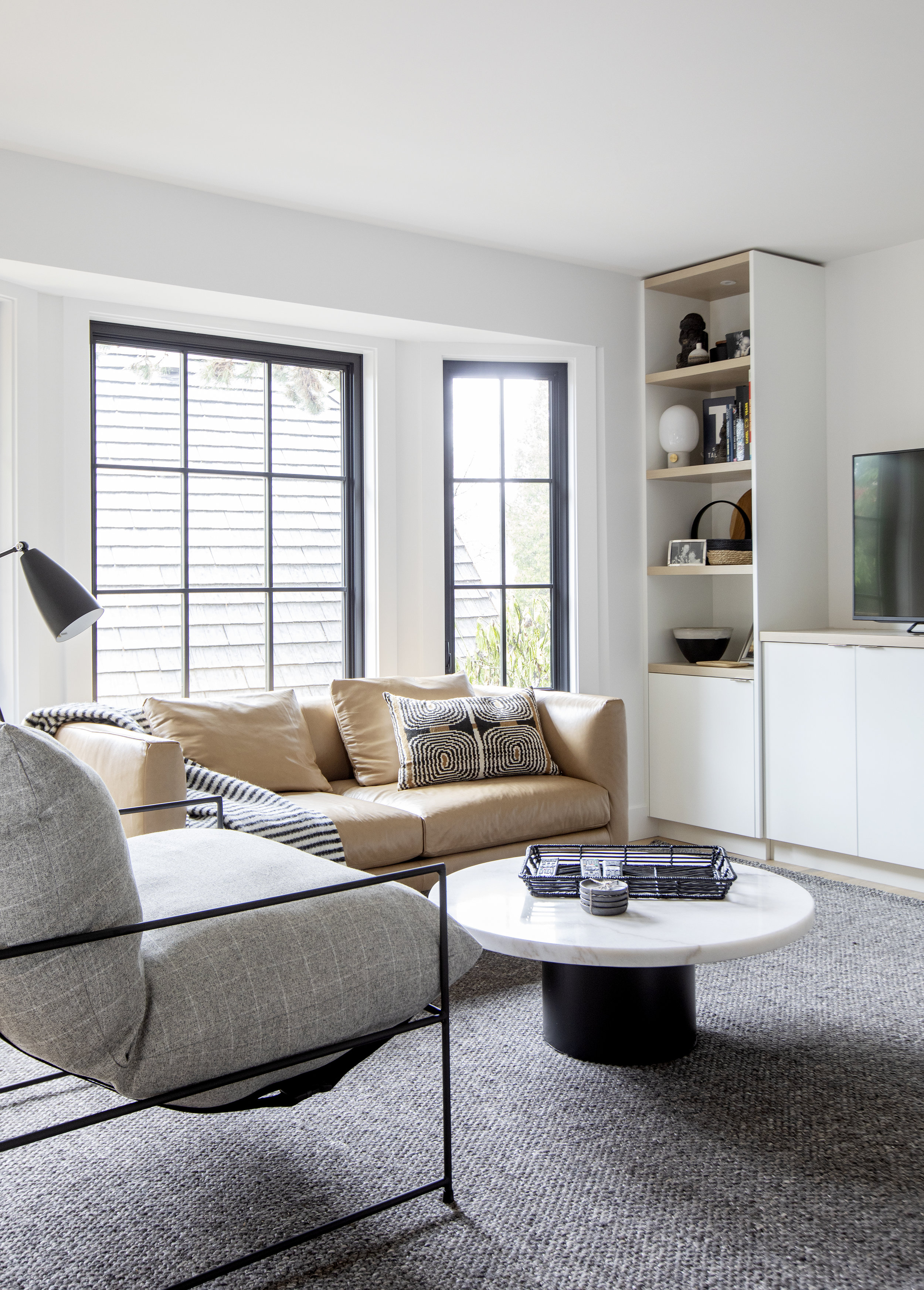The modern den in Alderfield Place features a comfy, yet modern looking armchair, and a tan loveseat. The room is pulled together with a large area rug.