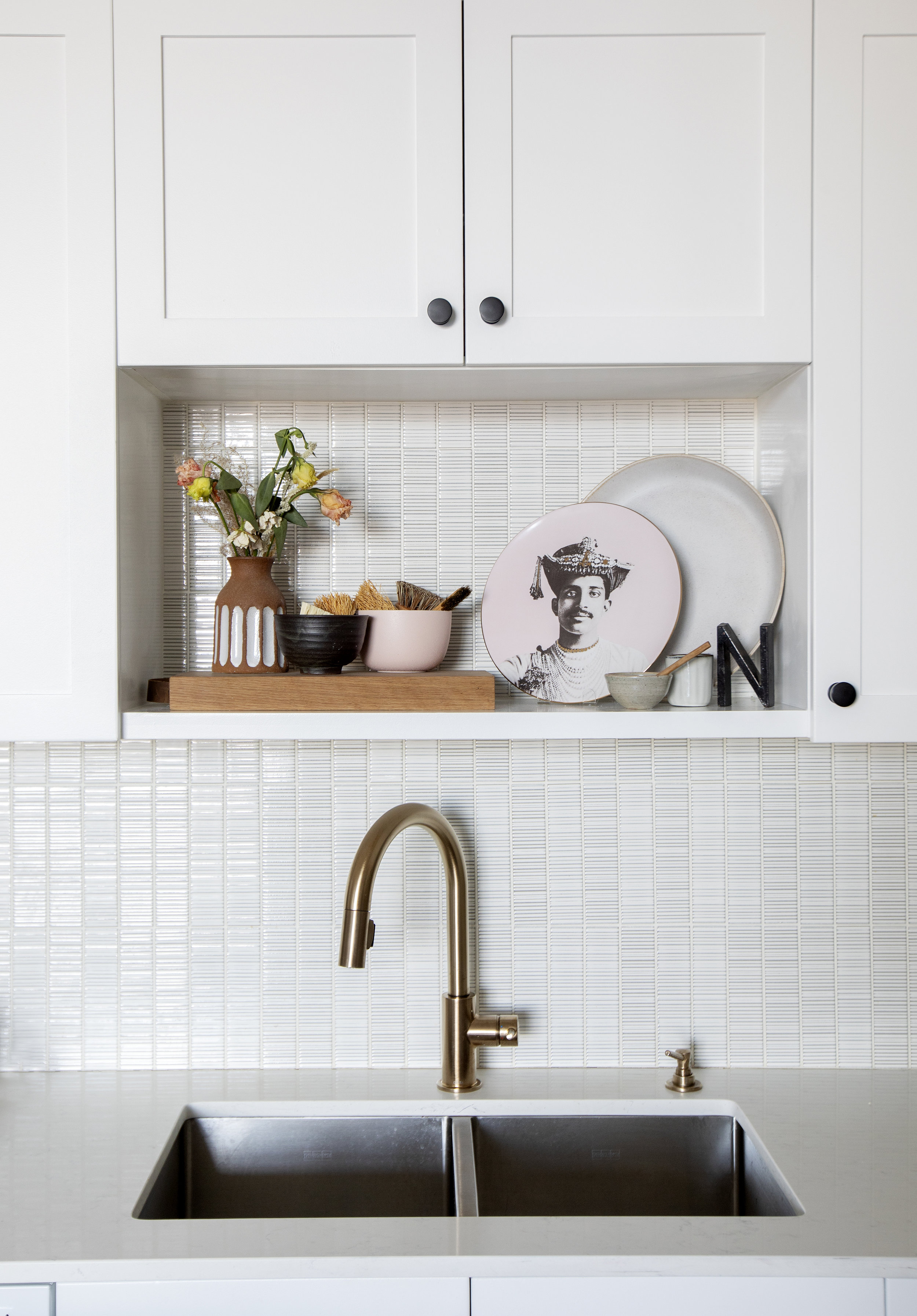 The kitchen sink at Prince Edward Street, including a tiled backspalsh and decorative shelf with interesting decor