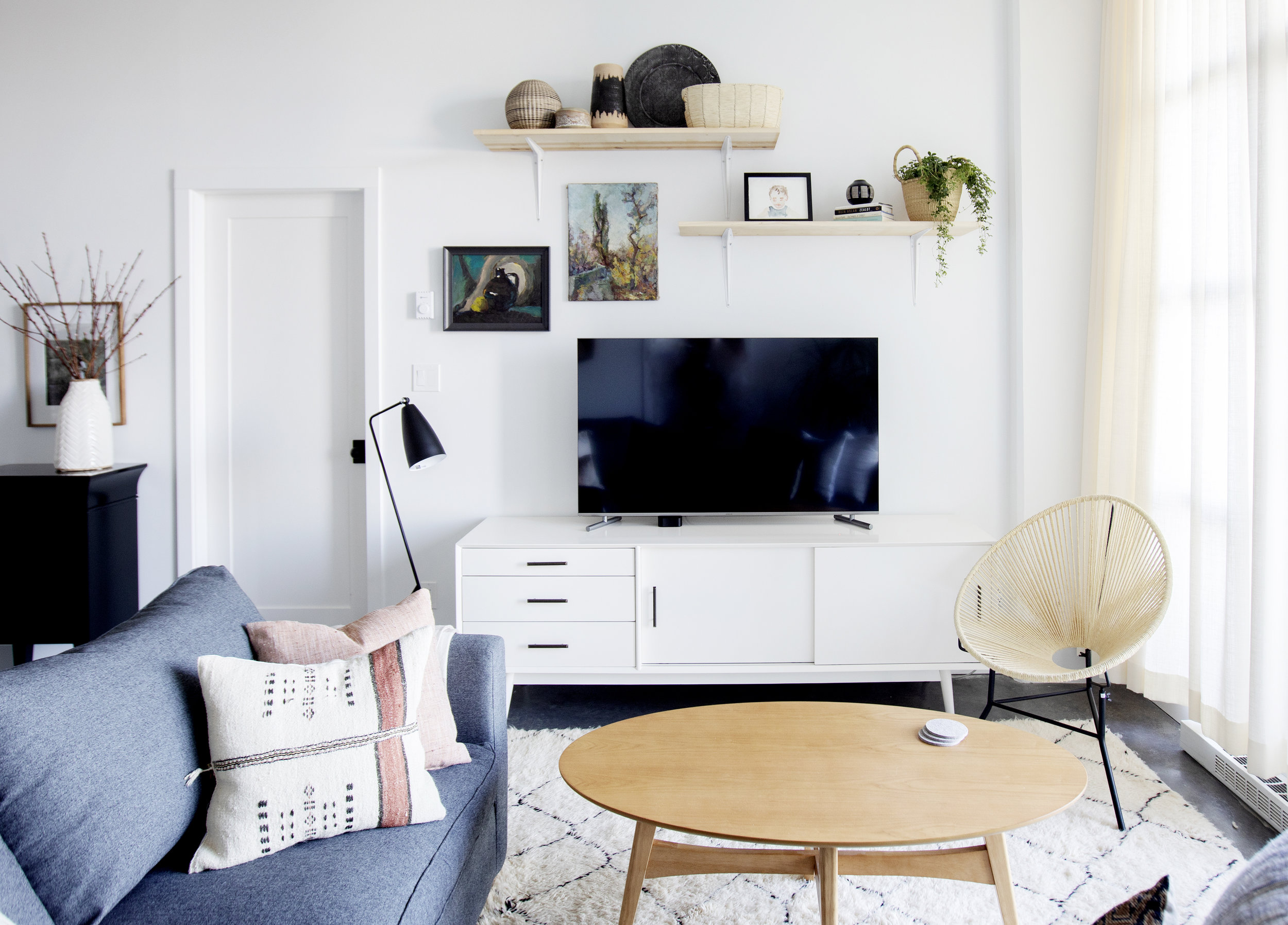 The living room of Prince Edward Street is bright and cozy, with tv on a white entertainment system, and shelving located above.