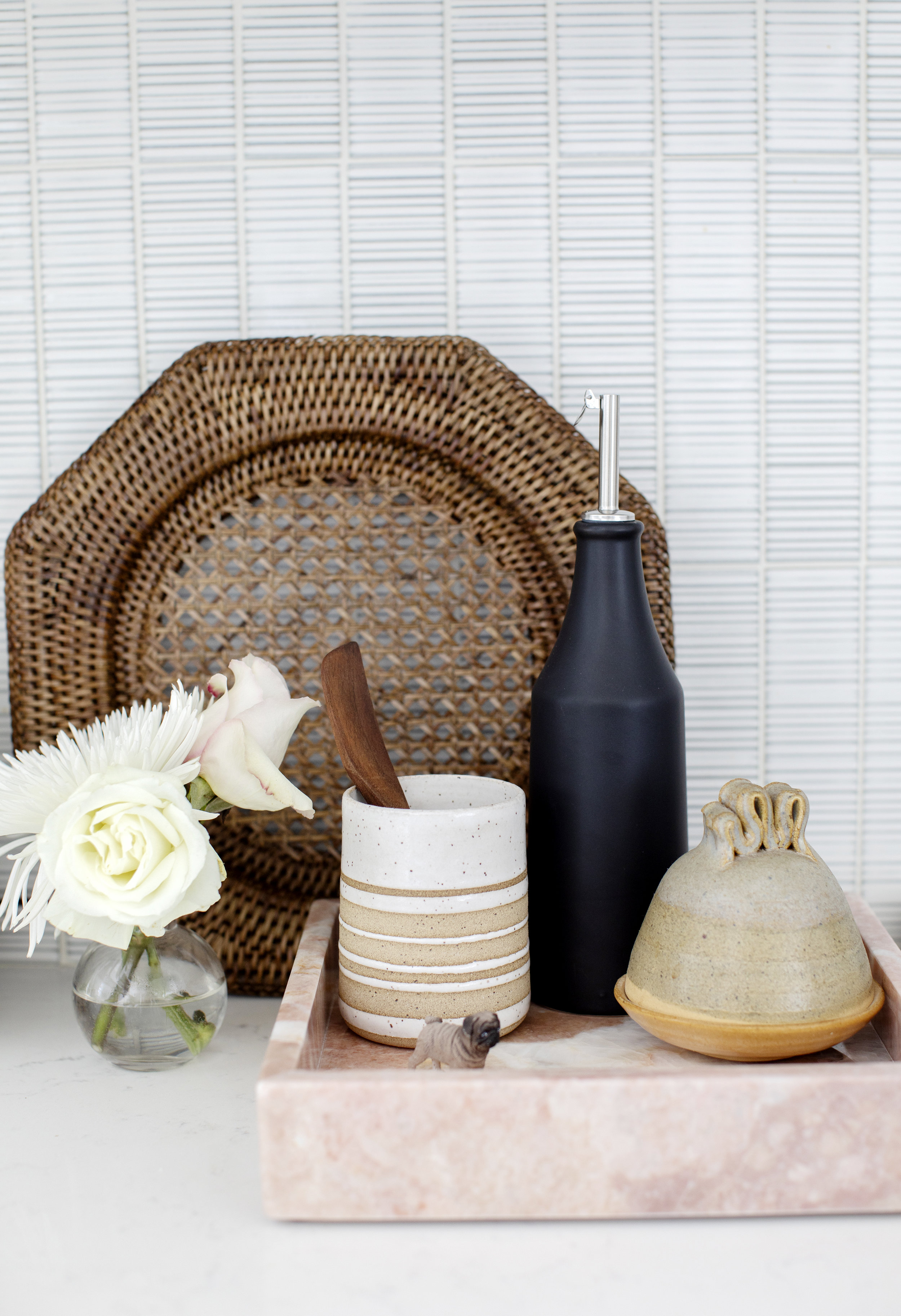 A close up shot of a decorative tray with kitchen pieces, including a wicker plate and a vase with roses