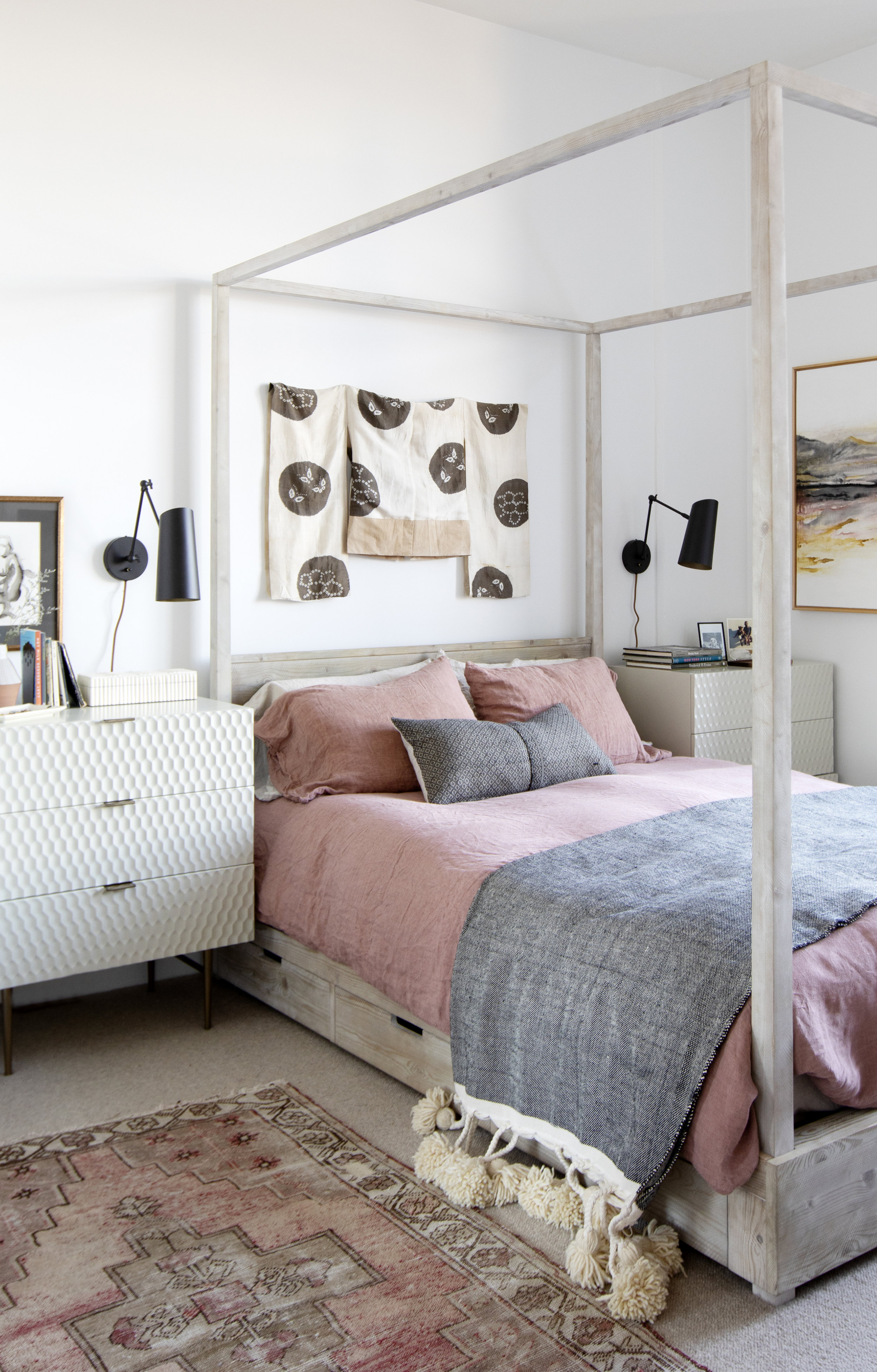 The master bedroom includes a four poster bed, with beautiful pink sheets and an accent rug.