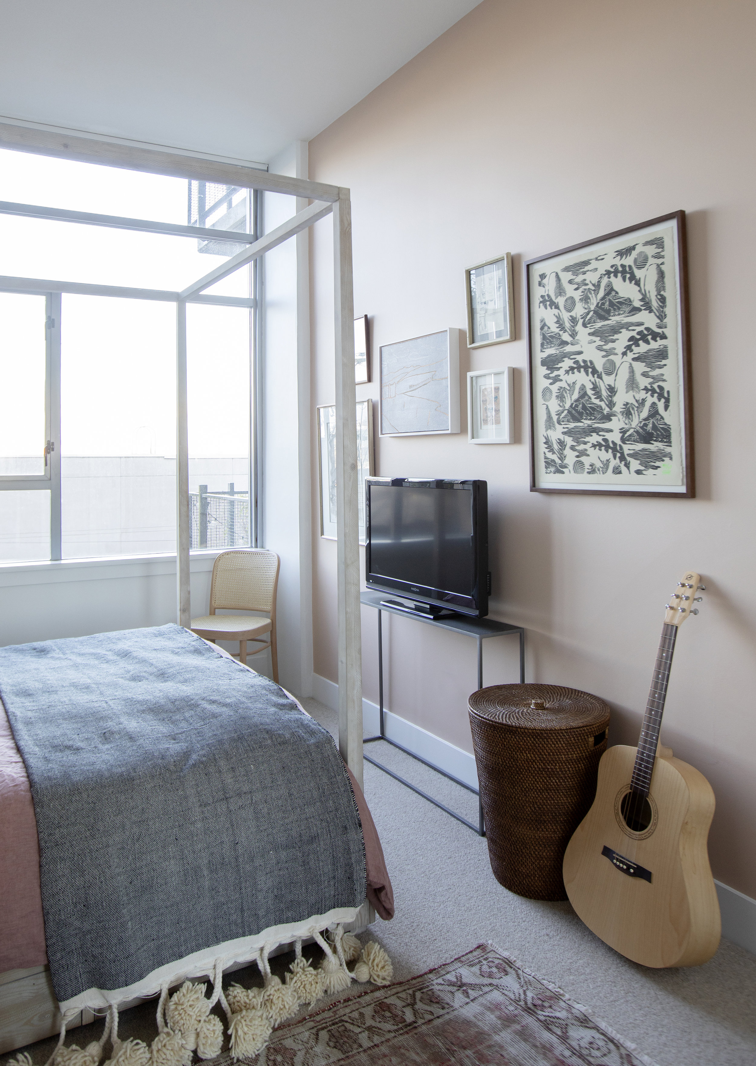 The view of the end of the bedroom, including a peach accent wall, and various paintings surrounding the tv located at the foot of the bed.