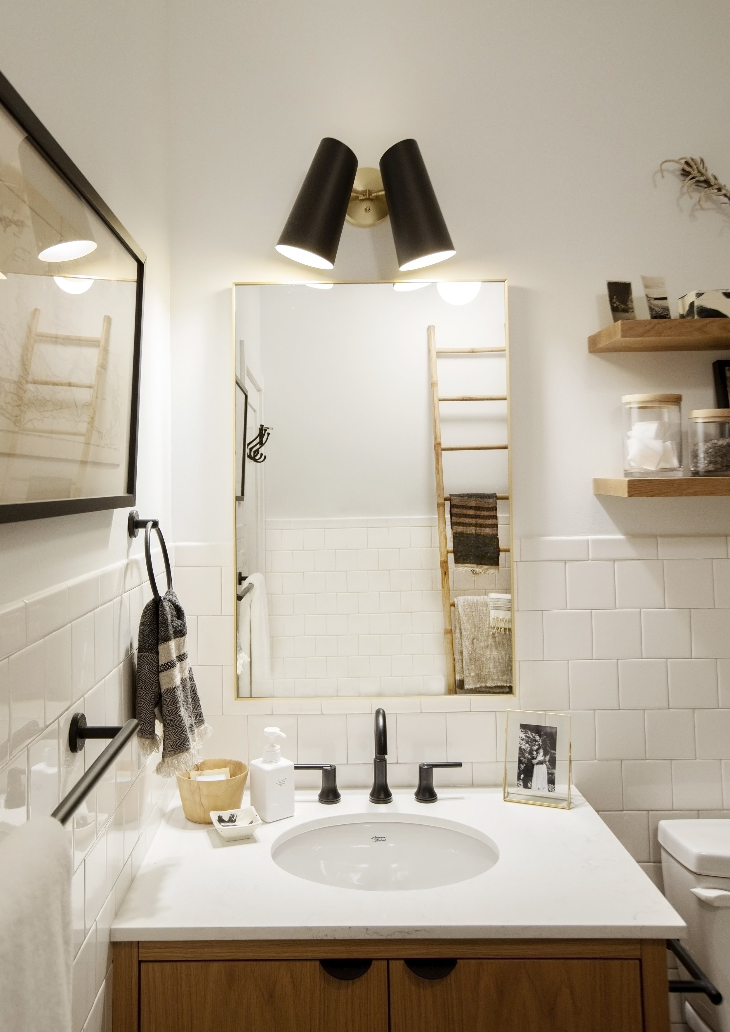 The bathroom at Alderfield Place has a beautiful gold mirror and black sconces hanging above
