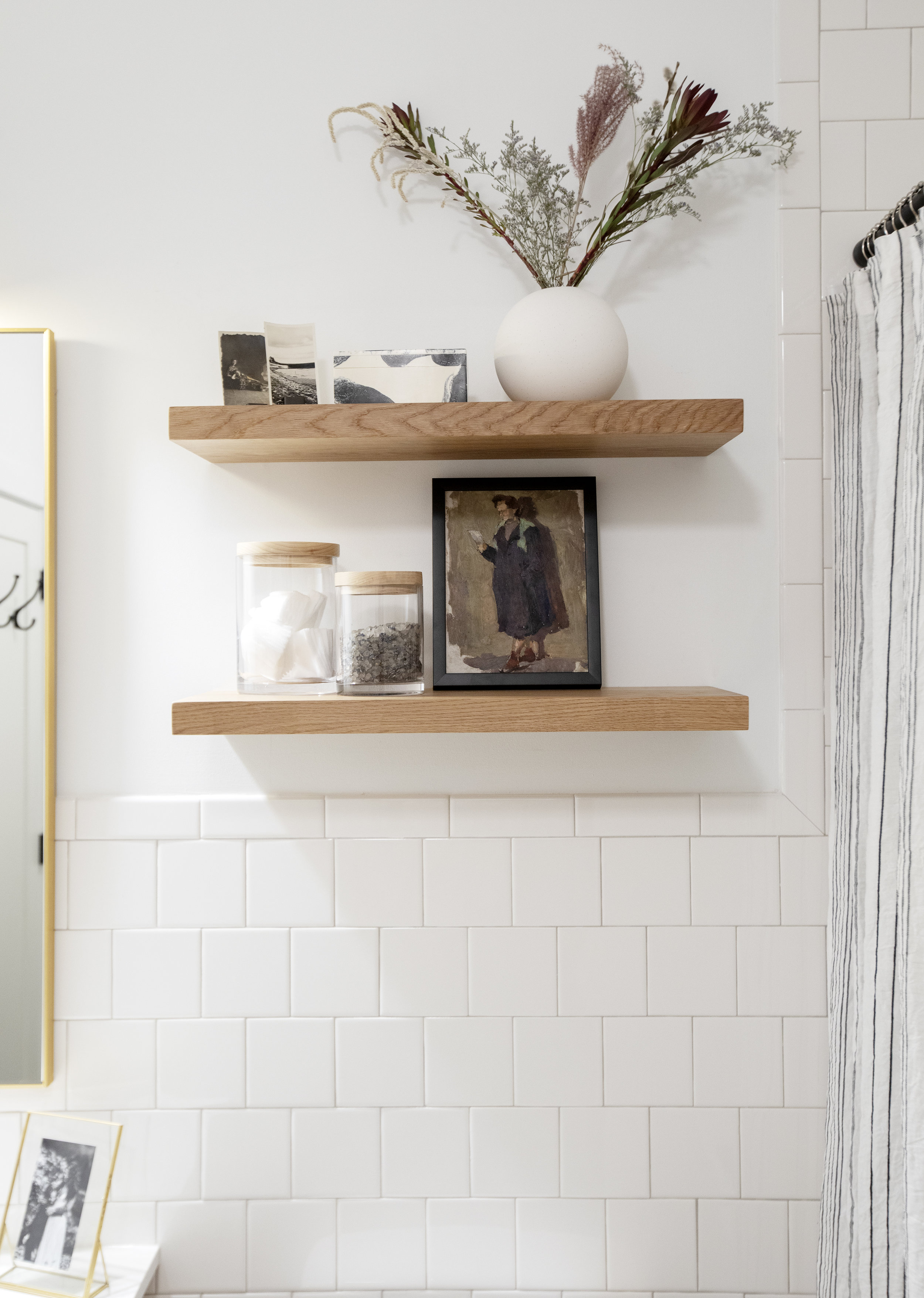 The bathroom of Prince Edward Street has two cherry wood shelves that have contain a decorative vase, a framed portrait and two lidded jars.