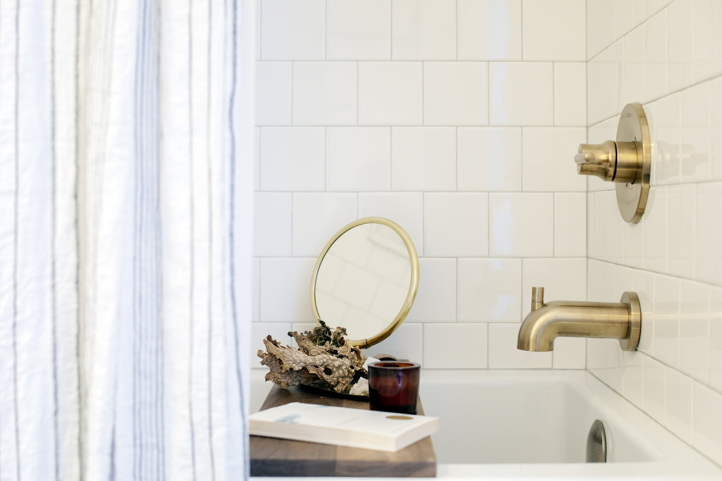 The tub in Prince Edward Street has gold fixtures and a rustic bathtub caddy with a gold mirror and a book.