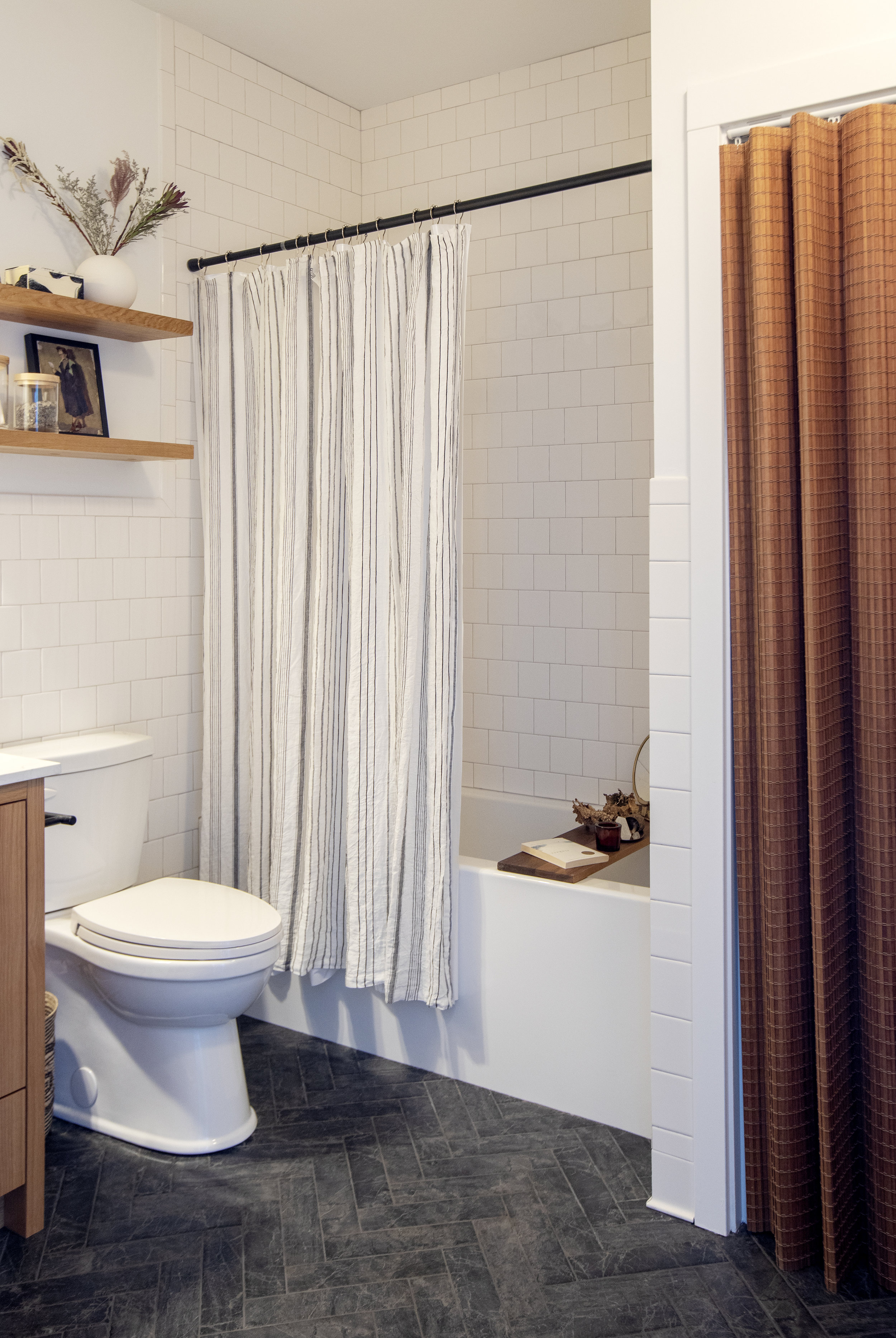 The bathroom at Prince Edward Street has beautiful white square tiles and dark tiled floors; a white and grey shower curtain hangs above the built in tub.