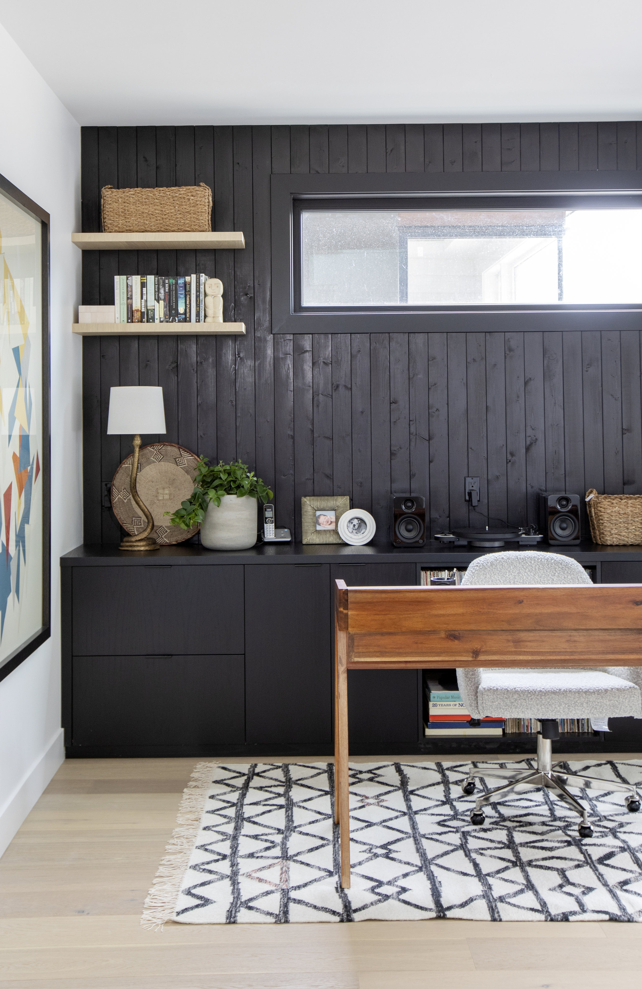 The study of East 13th Street has a dark panel accent wall behind a wooden writing desk.
