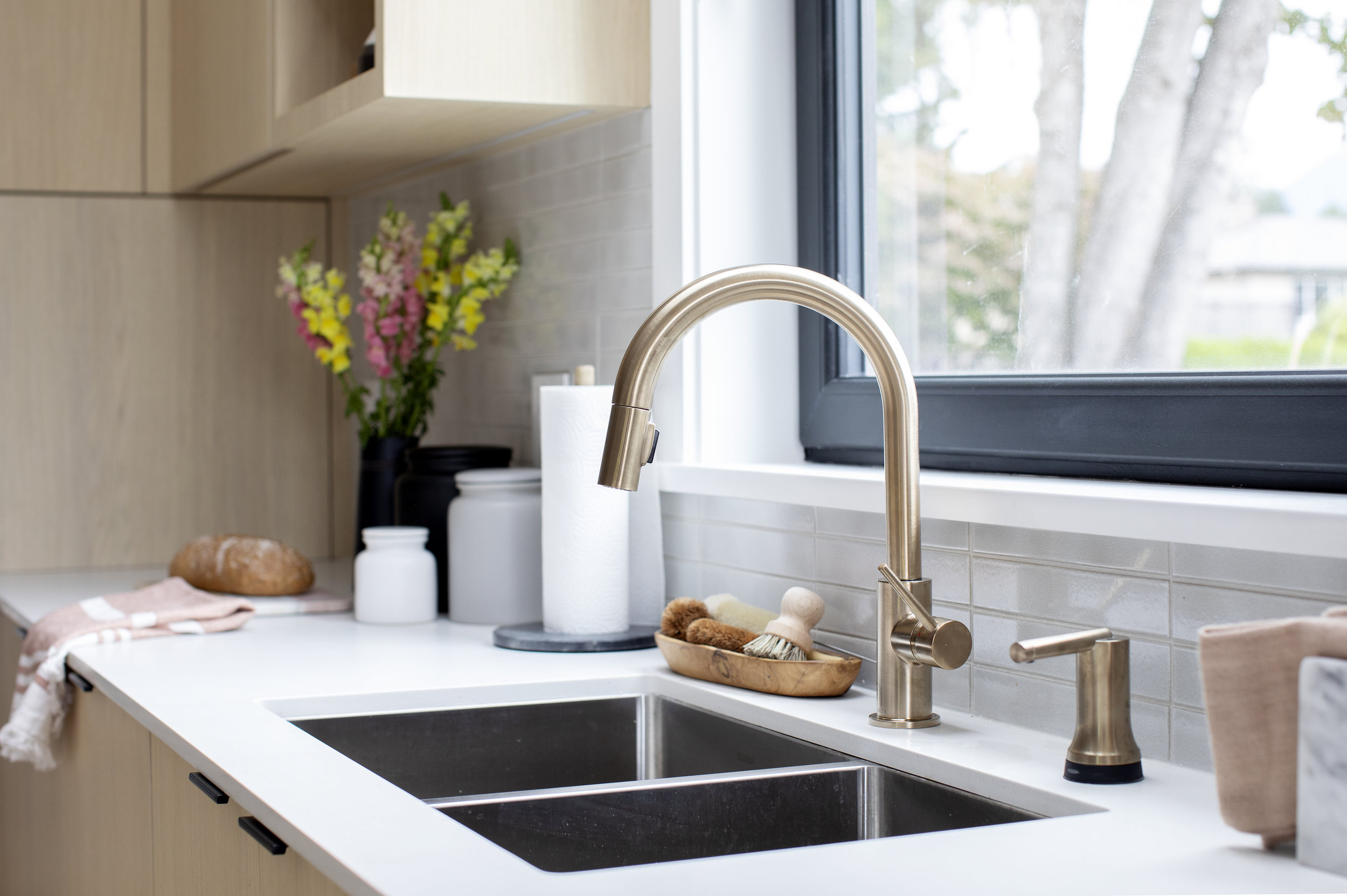 A decorative gold faucet adorns stainless steel double sinks