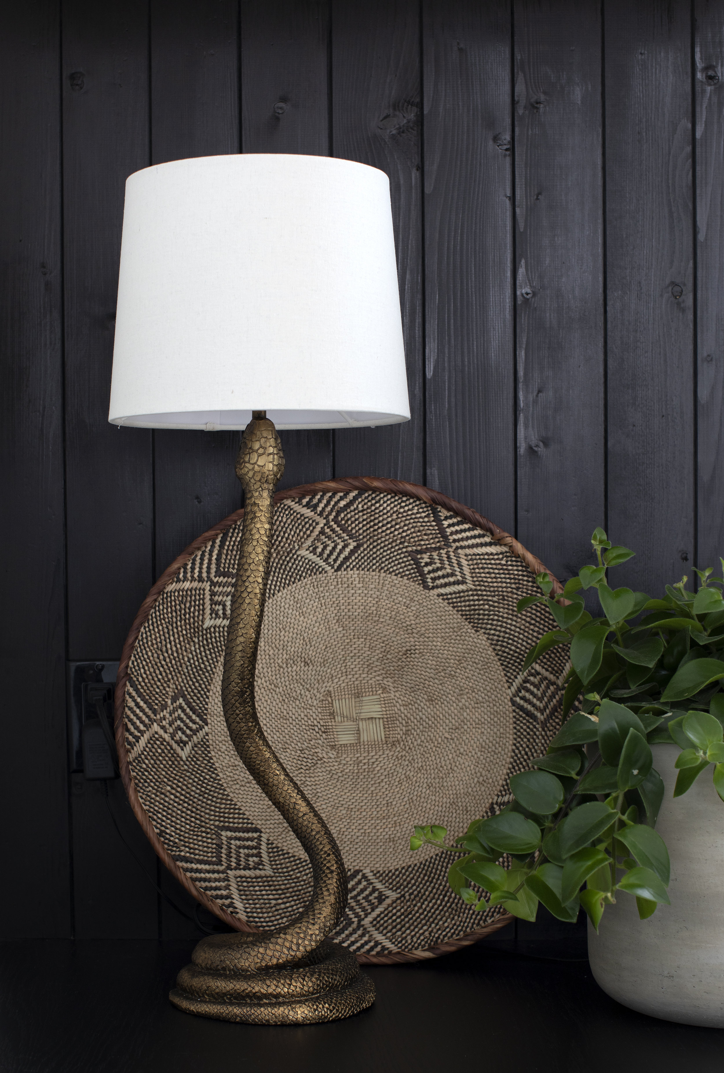 A beautiful white lamp with a brass snake base.